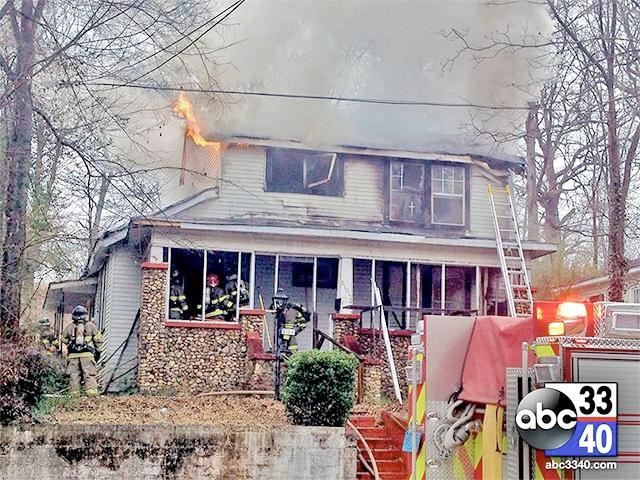 Birmingham firefighters working to extinguish a blaze at an East Lake home near the Birmingham airport, February 11, 2014.
