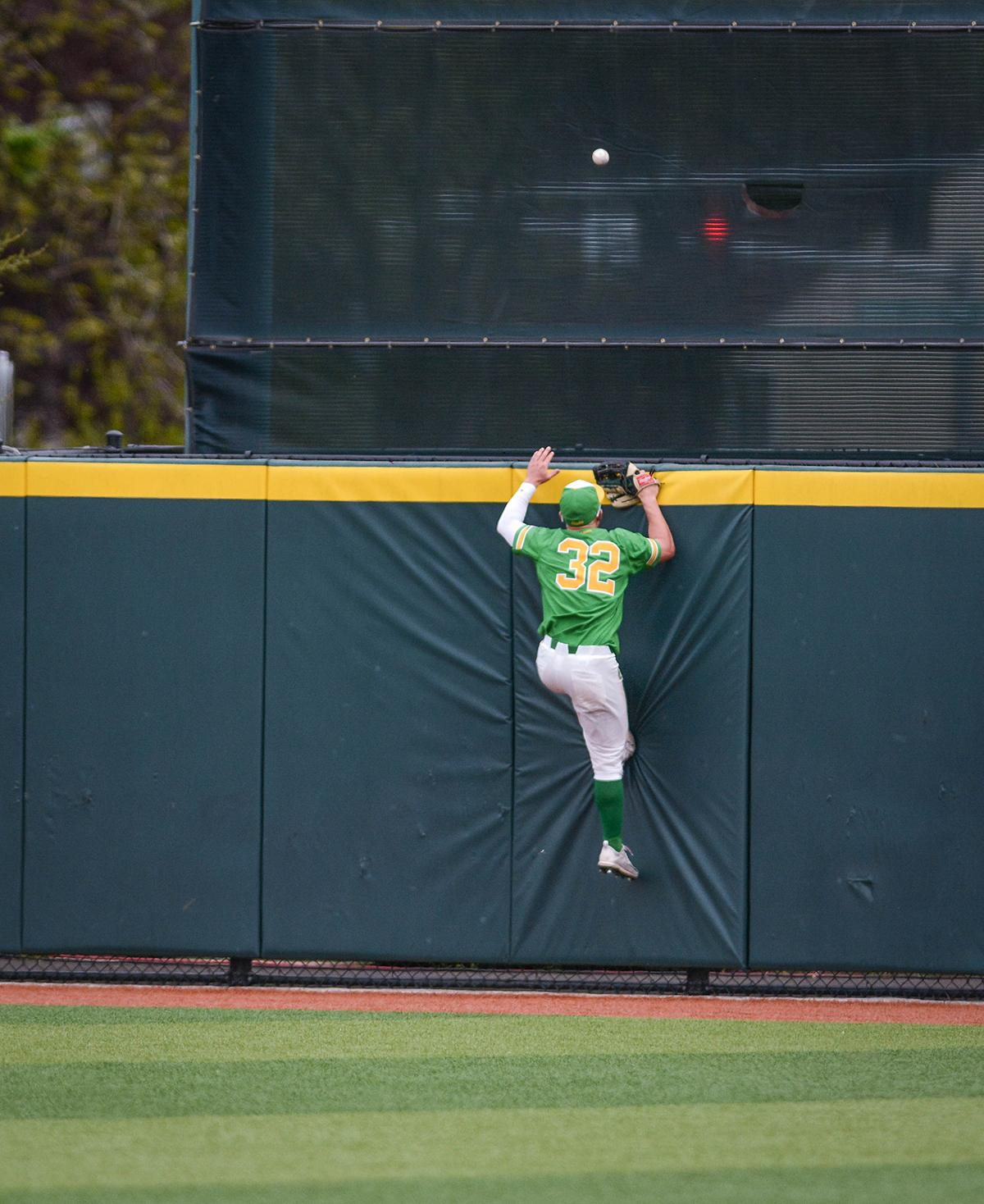 Ducks outfielder Jake Bennett (#32) climbs the wall to try and catch the homerun hit by Sun Devils Taylor Lane (#47). Despite a late comeback, the Ducks fall to Arizona State Sun Devils 4-3 in the second game of a three-game series. Photo by Jacob Smith, Oregon News Lab
