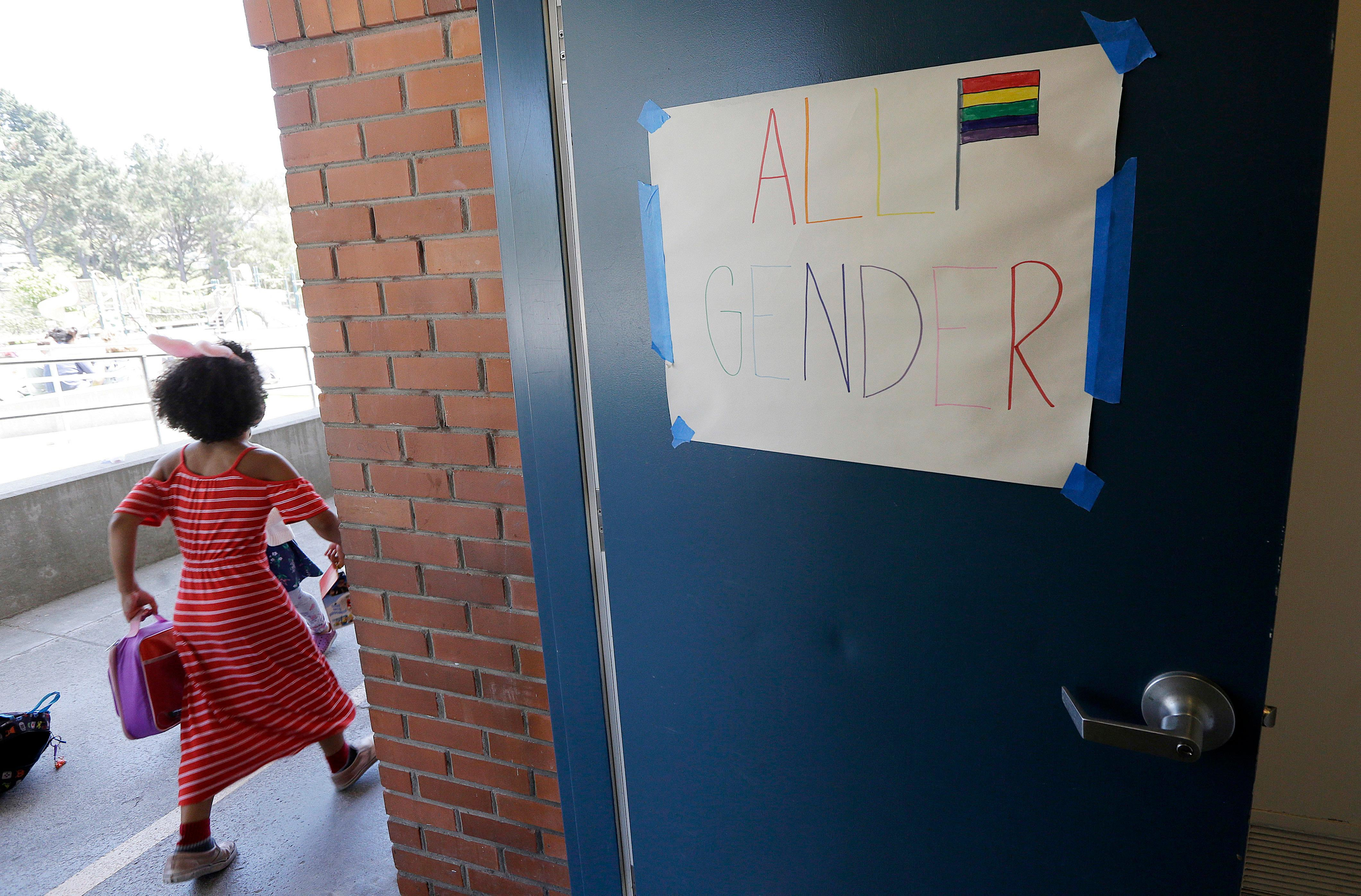 "In this Tuesday, July 11, 2017 photo, a camper walks past a sign for an all gender bathroom at the Bay Area Rainbow Day Camp in El Cerrito, Calif. The camp caters to transgender and ""gender fluid"" children, aged 4-12, making it one of the only camps of its kind in the world open to preschoolers, experts say. (AP Photo/Jeff Chiu)"