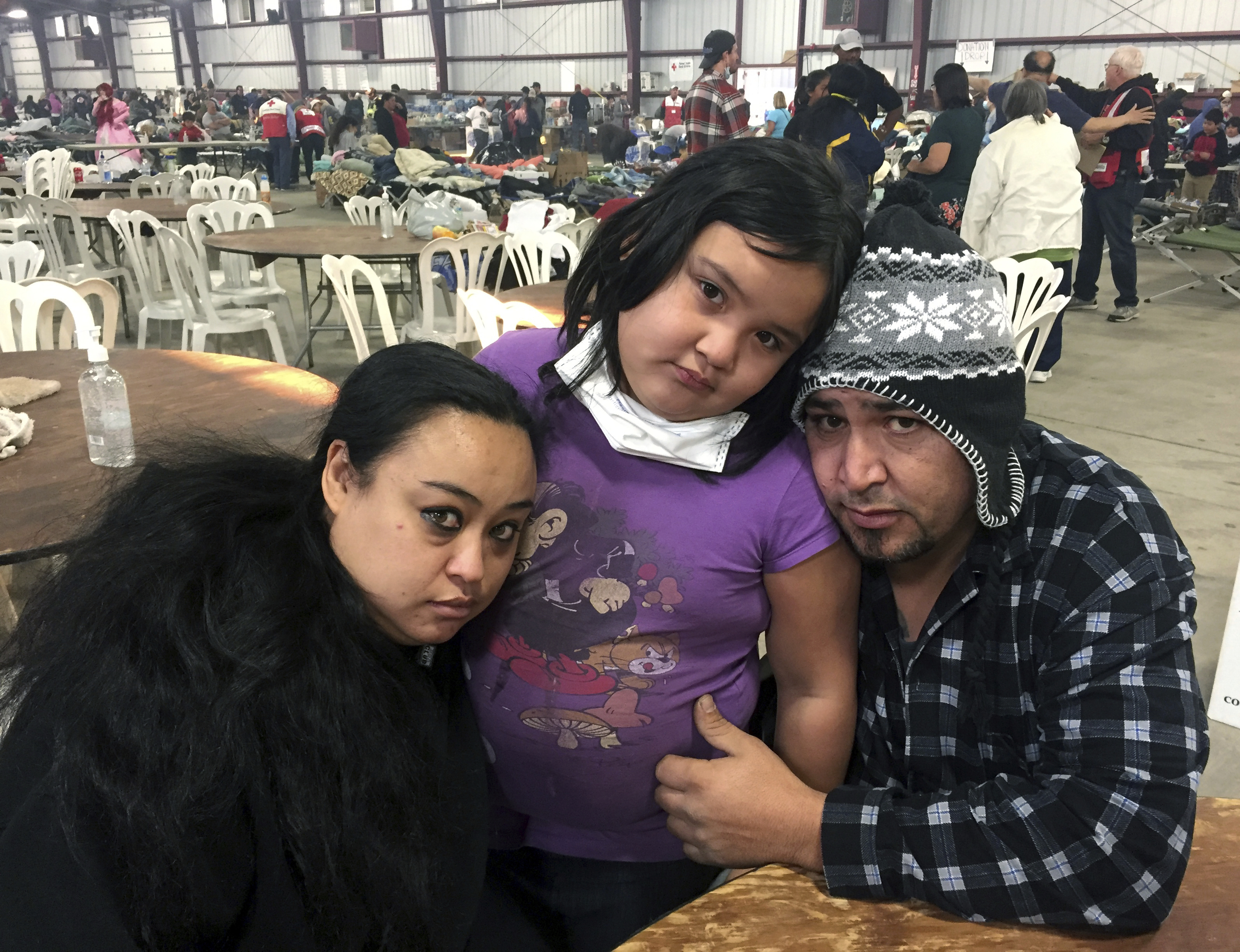FILE - In this Dec. 6, 2017, file photo wildfire survivors, Marolyn Romero-Sim, left, with Hugo Romero-Rodriguez, center, and their 9-year-old daughter, Milagros, sit inside the evacuation center at the Ventura County Fairgrounds in Ventura, Calif. The family has been at the shelter for two weeks after they watched their home of four years, an RV, burn in the wildfire, along with their beloved dog, their Christmas tree and a few presents. (AP Photo/Amanda Lee Myers, File)