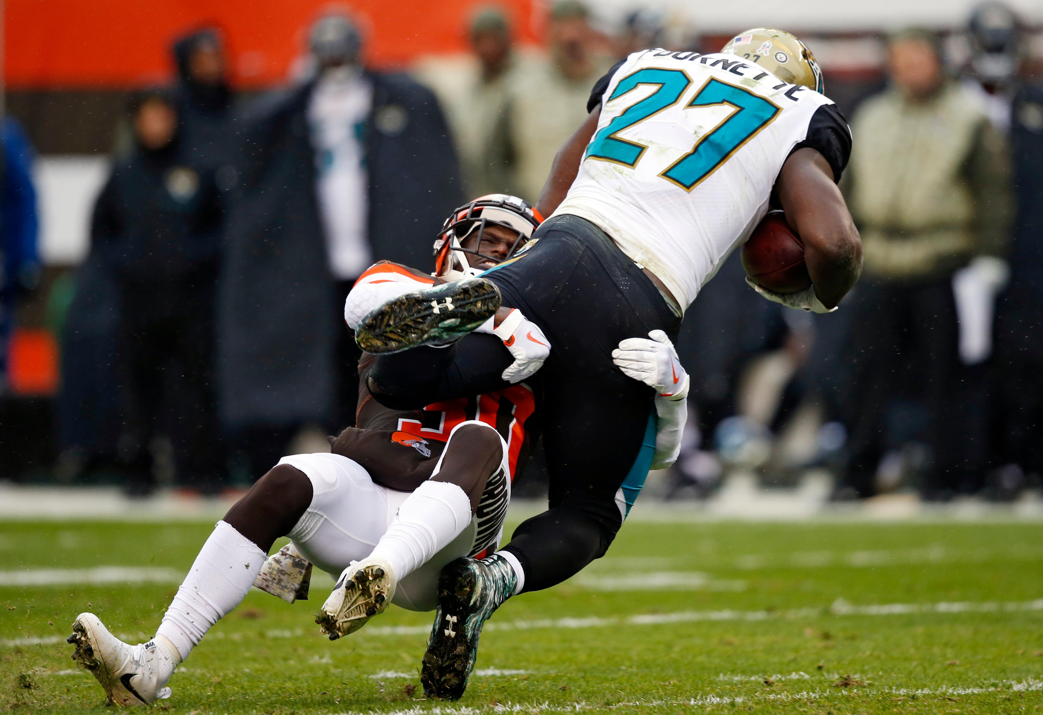 Cleveland Browns defensive back Jason McCourty (30) tackles Jacksonville Jaguars running back Leonard Fournette (27) in the first half of an NFL football game, Sunday, Nov. 19, 2017, in Cleveland. (AP Photo/Ron Schwane)