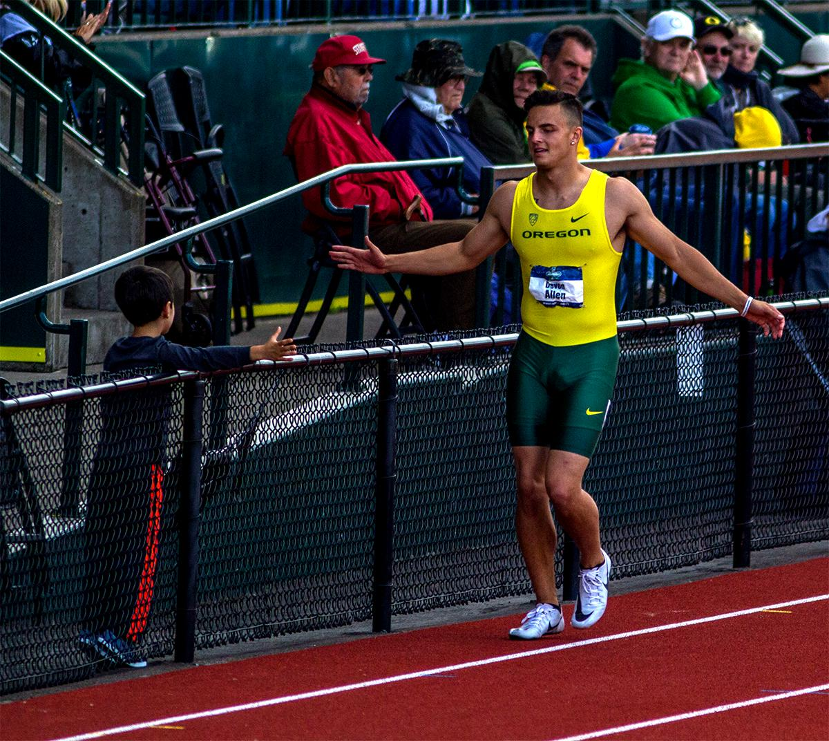 Devon Allen high fives a fan during his victory lap after winning the 110 meter hurdles in 13.50.  Photo by August Frank, Oregon News Lab