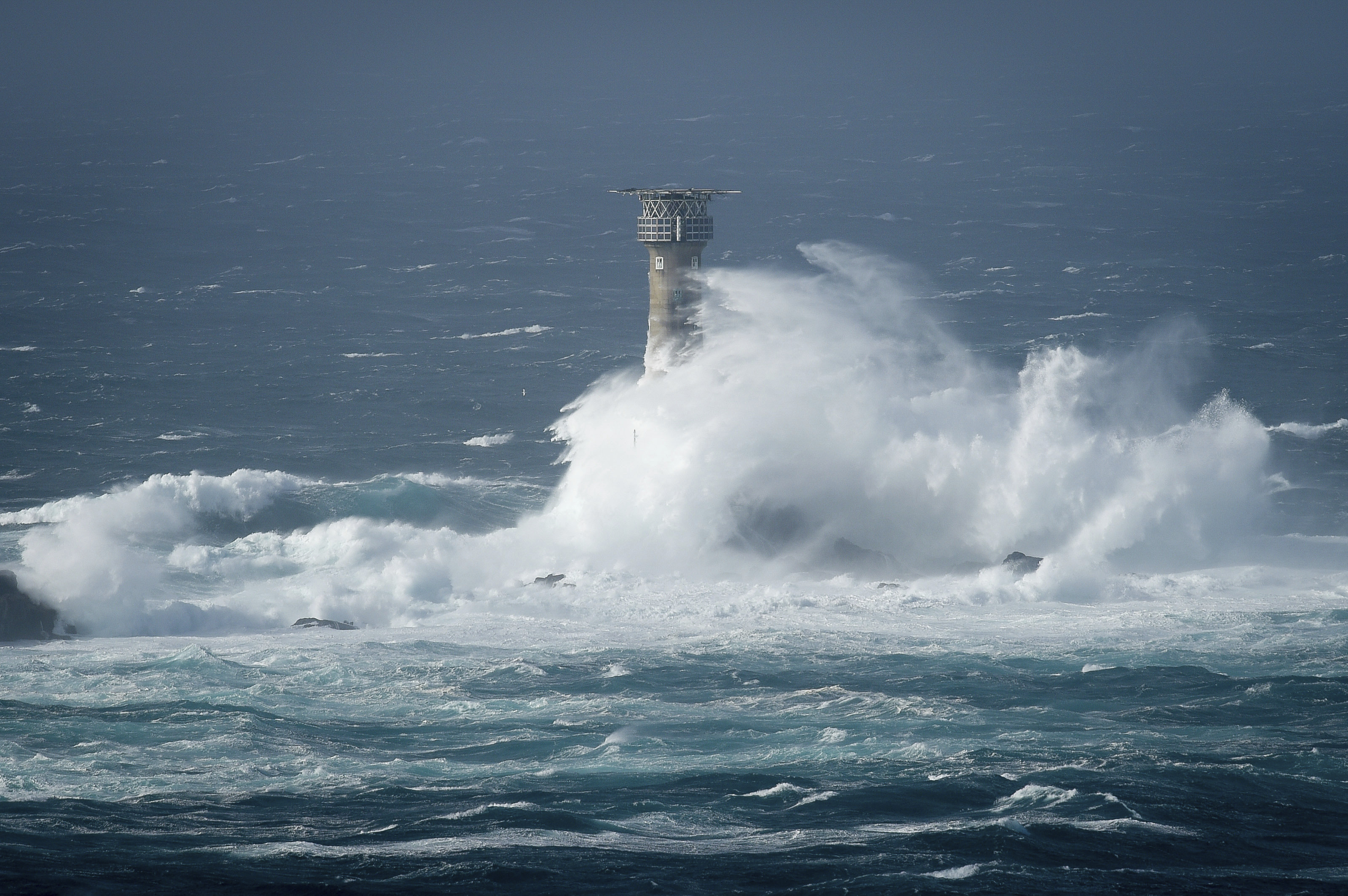 Waves break on Longships lighthouse off the coast of Lands End, southwestern England, as the remnants of  Hurricane Ophelia begins to hit parts of Britain and Ireland. Ireland's meteorological service is predicting wind gusts of 120 kph to 150 kph (75 mph to 93 mph), sparking fears of travel chaos. Some flights have been cancelled, and aviation officials are warning travelers to check the latest information before going to the airport Monday.  (Liam McBurney/PA via AP)