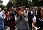 A woman speaks on her cellphone as people evacuated from office building gather in Reforma Avenue after an earthquake in Mexico City, Tuesday Sept. 19, 2017.
