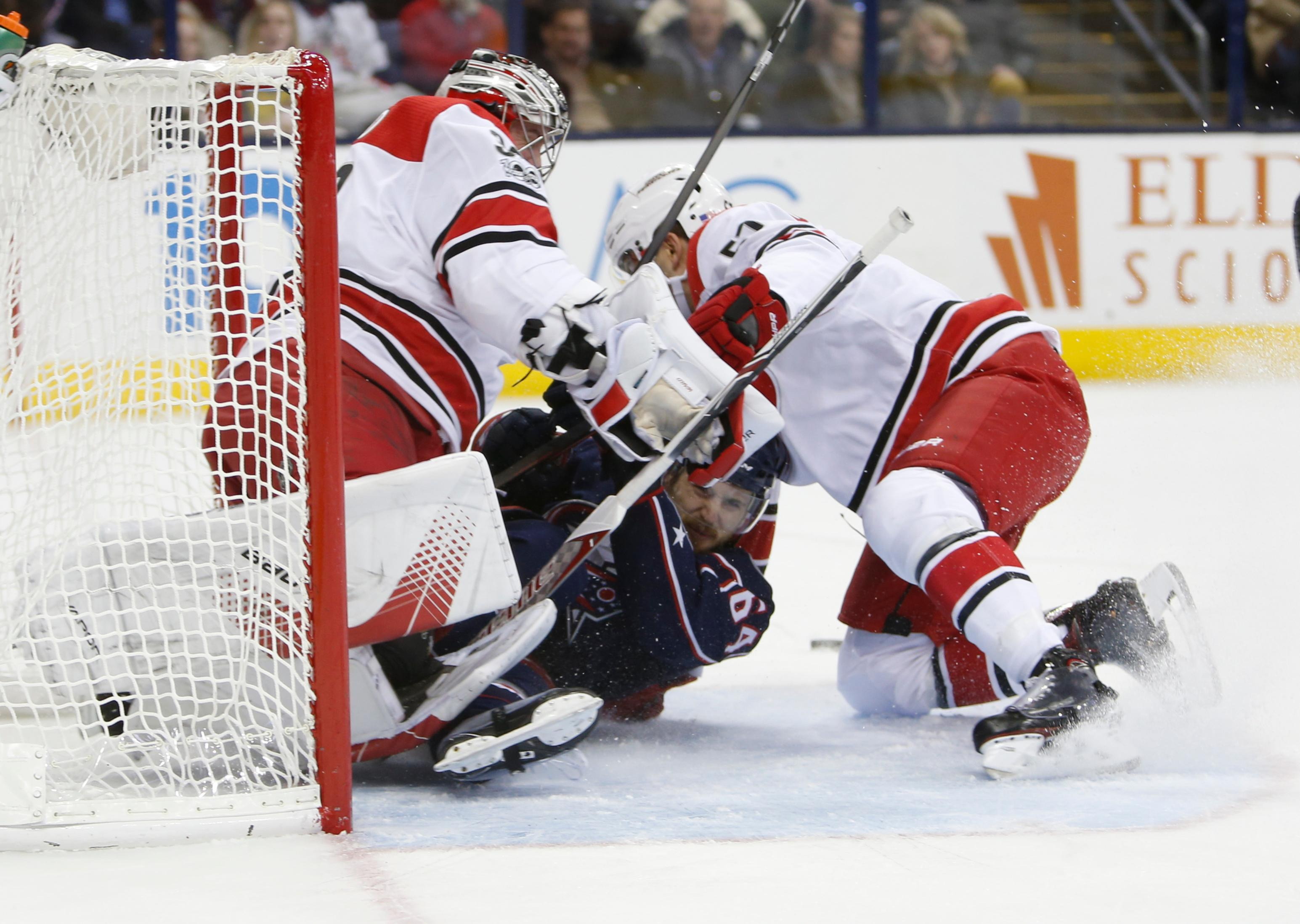 Carolina Hurricanes' Trevor van Riemsdyk, right, holds Columbus Blue Jackets' Tyler Motte as they collide with goaltender Cam Ward during the second period of an NHL hockey game Friday, Nov. 10, 2017, in Columbus, Ohio. van Riemsdyk was penalized on the play. (AP Photo/Jay LaPrete)