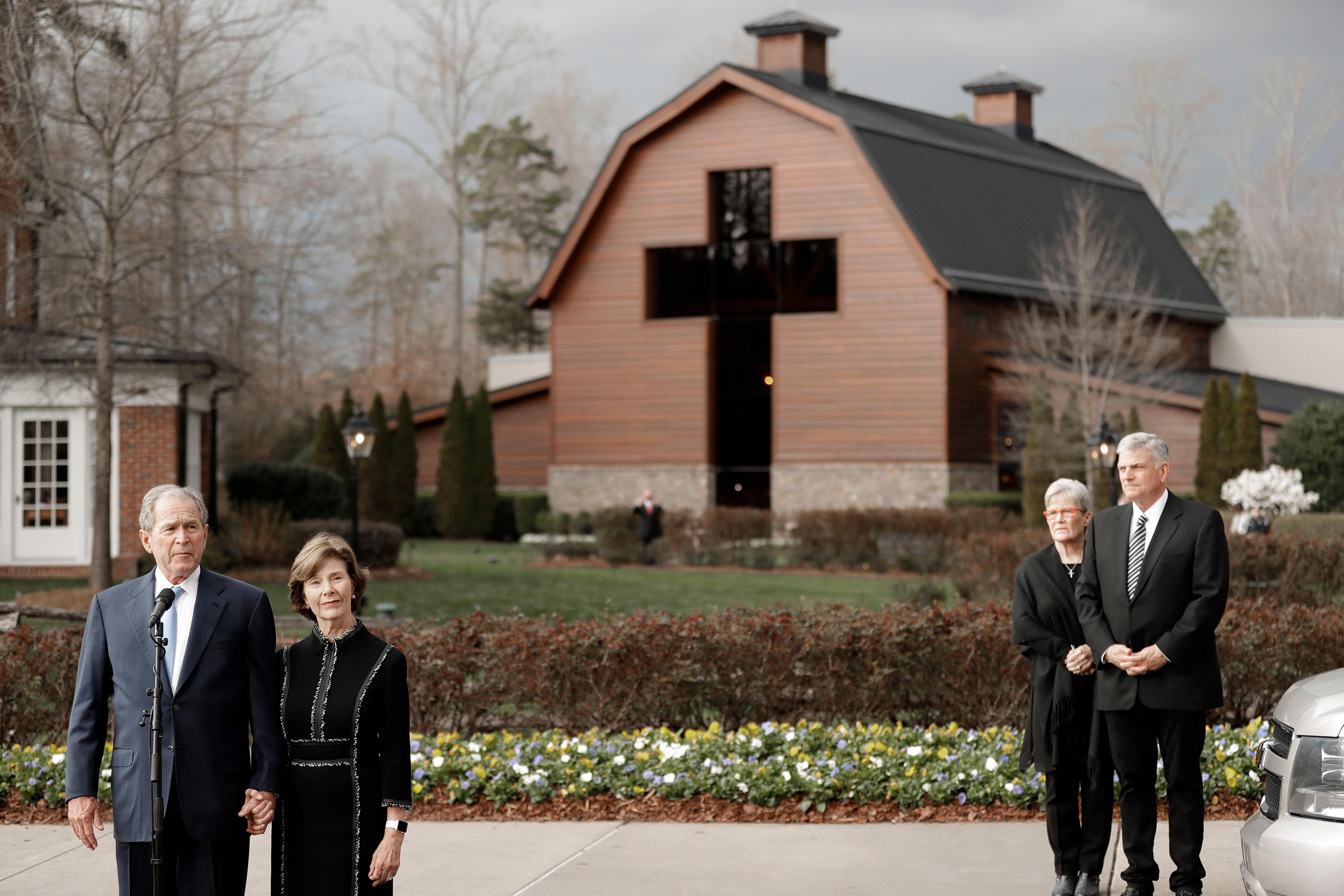 Former President George W. Bush, left, speaks to the media as wife Laura Bush, left, and Franklin Graham, back right, and his wife Jane Graham, back left, listen after paying their respects to Billy Graham during a public viewing at the Billy Graham Library in Charlotte, N.C., Monday, Feb. 26, 2018. (AP Photo/Chuck Burton)