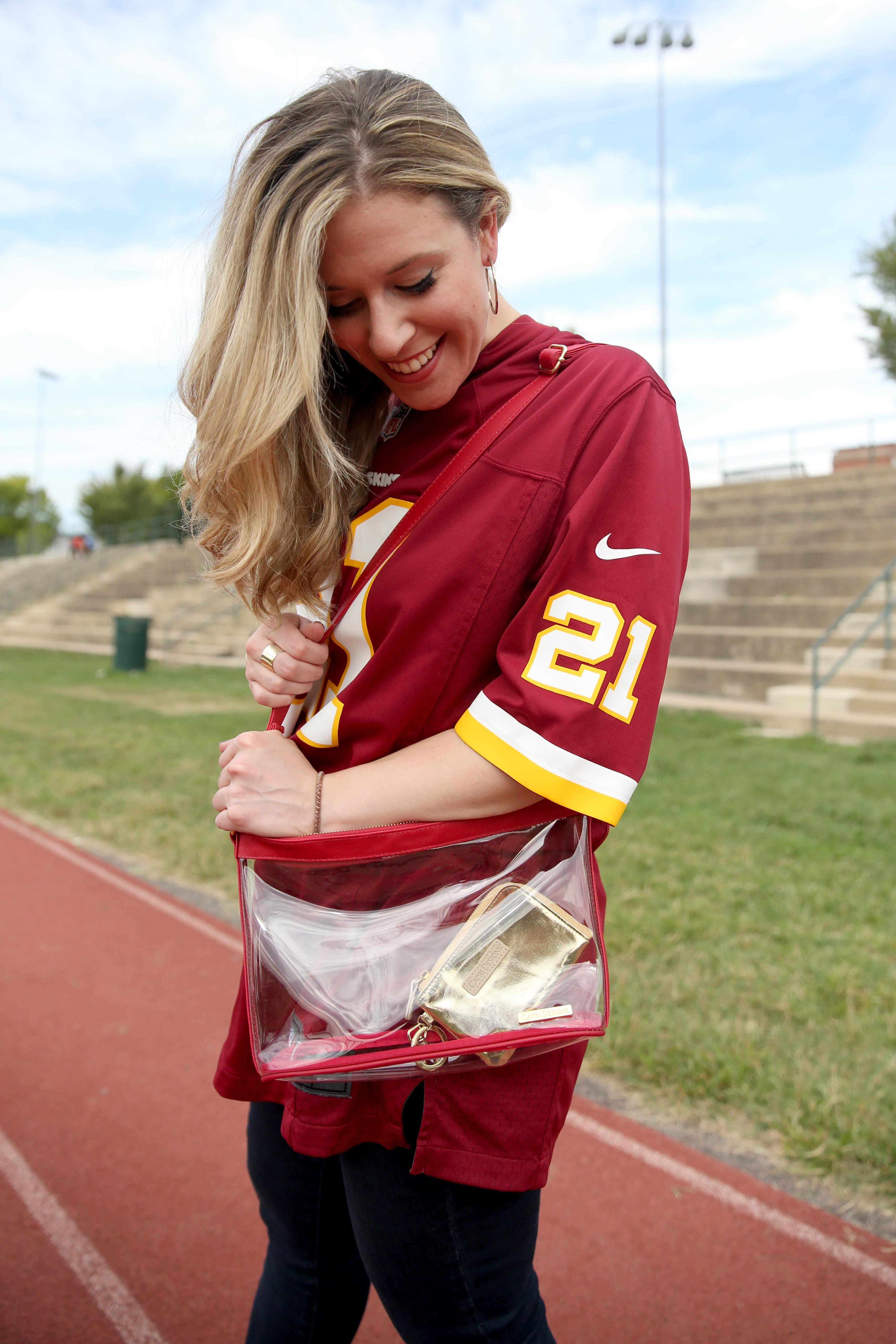 If you are going to the game it's important to remember they only allow tiny purses. Anything bigger than a wallet basically needs to be clear! I recommend one of these clear, hip, plastic, cross body bags.  This one is by a company called Capri Designs. I like it because it's a burgundy-trimmed bag with a little gold card holder. I couldn't be more redskins ready!(Image: Amanda Andrade-Rhoades/ DC Refined)