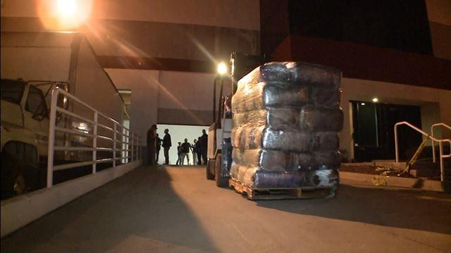Drug officials move a pallet loaded full of seized narcotics.