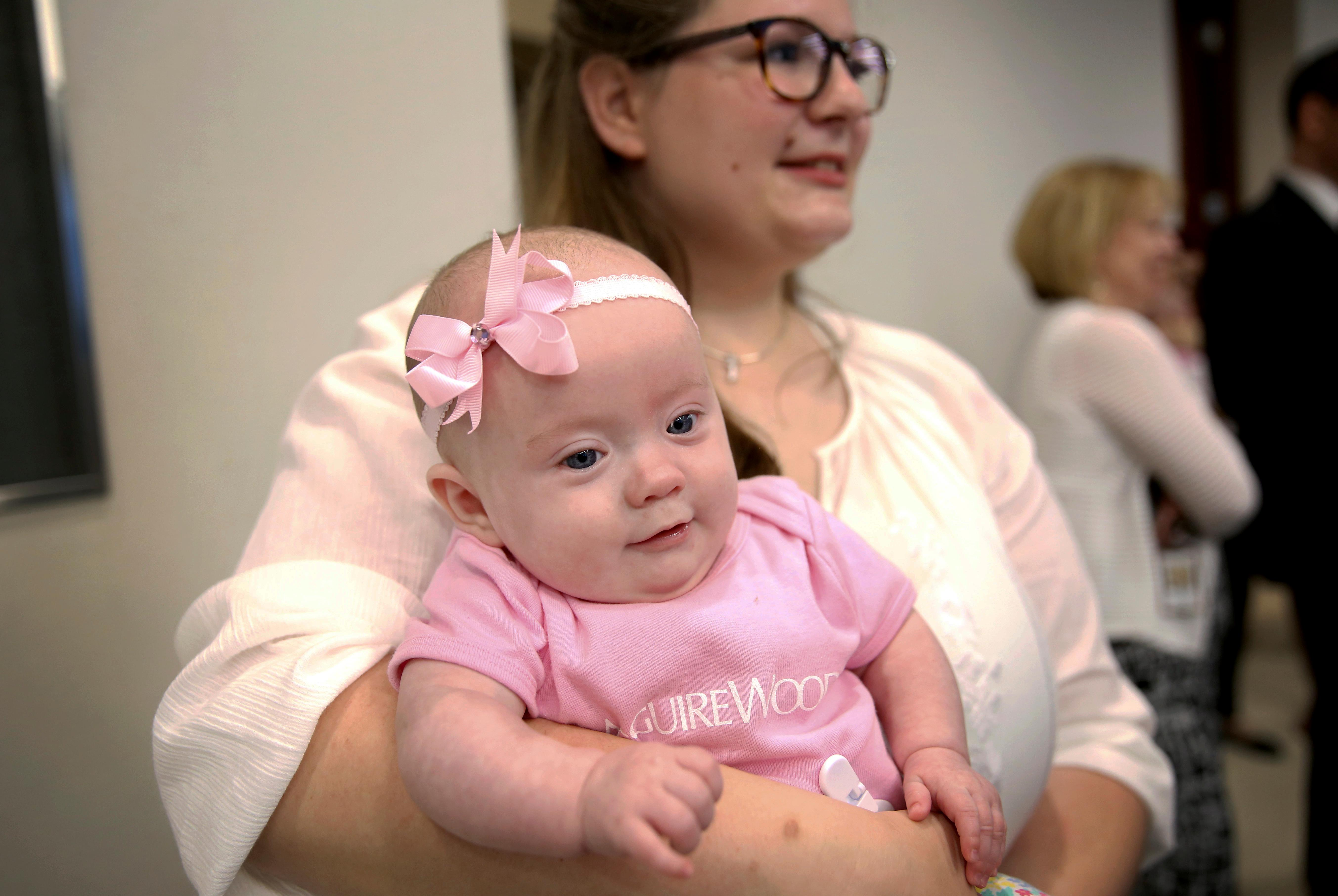 "Merle Wittig, one of the Baudinet family au pairs, holds Ava Louise Baudinet while the family is greeted at McGuireWoods on Tuesday May 16, 2017, in Richmond, Va. The Baudinet quintuplets made their public debut Tuesday in Richmond. Ava Louise, Clara Catherine, Camille ""Millie"" Whitney, Luke Thomas, and Isabelle Frances were born Dec. 4 in Arizona.   (Shelby Lum/Richmond Times-Dispatch via AP)"