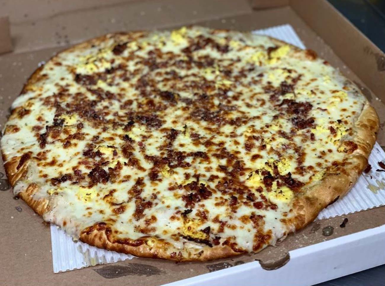 Breakfast Pizza: homemade sausage gravy, scrambled eggs, bacon, and melted cheese / Image courtesy of Poseidon's Pizza Company // Published: 7.8.20