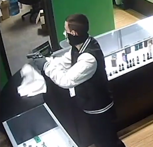 The gunman was wearing a mask, a letterman-style jack with a block body and white leather sleeves, black gloves, dark pants and red Converse shoes. The owner of the store said the robber made off with $1,700 in cash and merchandise. Anyone with information in the case is asked to call (541) 682-5111. (From submitted video)