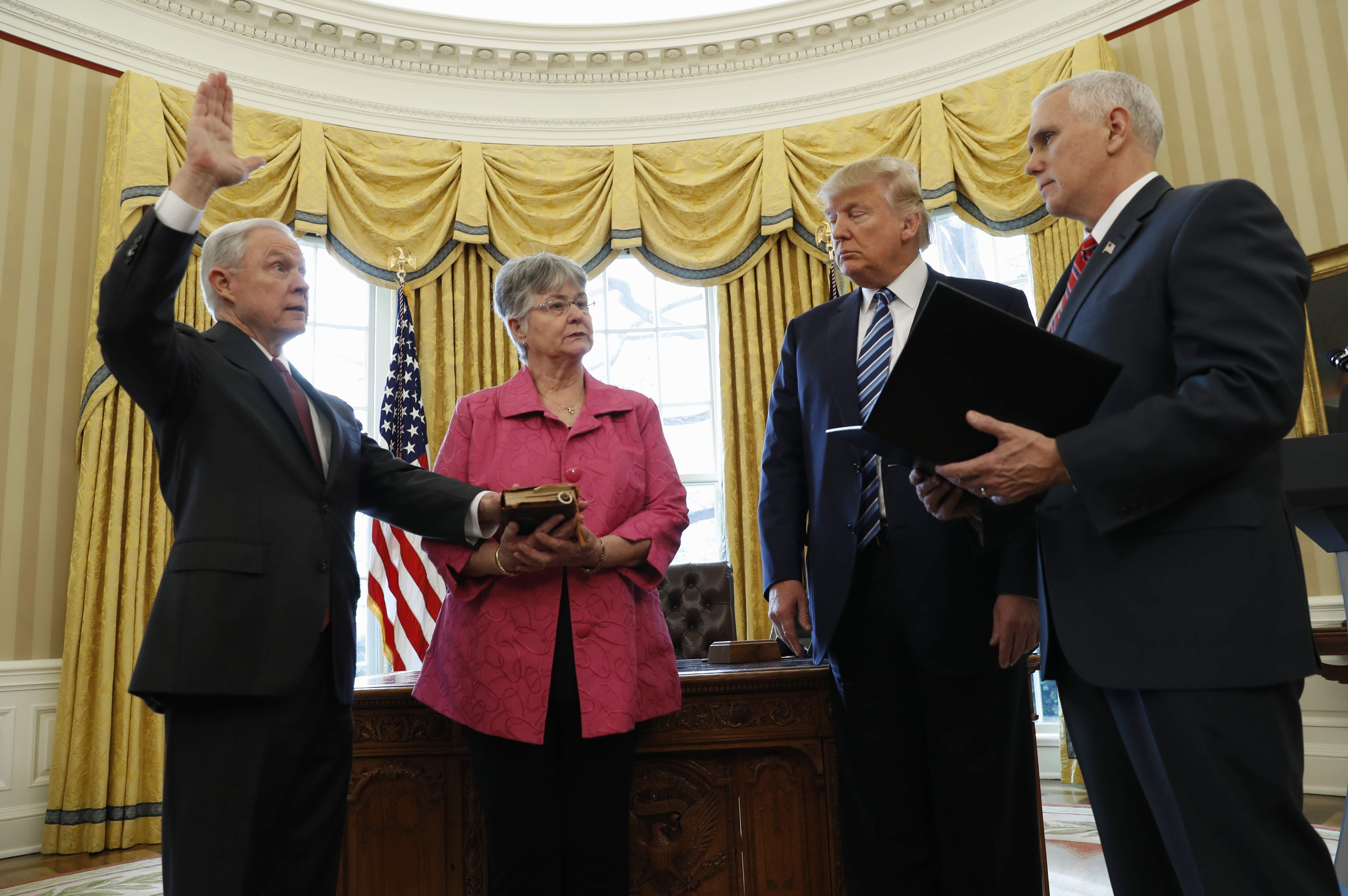 DAY 21 - In this Feb. 9, 2017, file photo, President Donald Trump watches as Vice President Mike Pence administers the oath of office to Attorney General Jeff Sessions, accompanied by his wife Mary, in the Oval Office of the White House in Washington. (AP Photo/Pablo Martinez Monsivais, File)