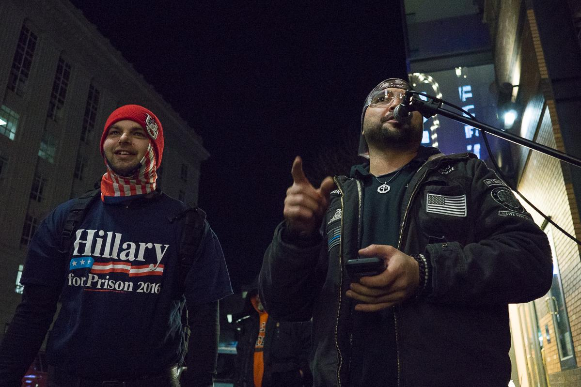 Patriot Prayer leader Joey Gibson (right) addresses his fellow demonstrators with a PA system the group had set up on the corner of SW Main Street and SW Broadway. The alt-right group Patriot Prayer protested Hillary Clinton's Portland speaking engagement outside the Arlene Schnitzer Concert Hall on Tuesday, December 12. Their demonstration was met with a counter-protest by Antifa, and the two groups traded insults and jeers across SW Main Street from 6:00 p.m. until the event's conclusion at approximately 9:30 p.m. Throughout the evening, both Patriot Prayer and Antifa sporadically marched around the theater. At least one scuffle occurred during one such march. Photo by Kit MacAvoy, Oregon News Lab