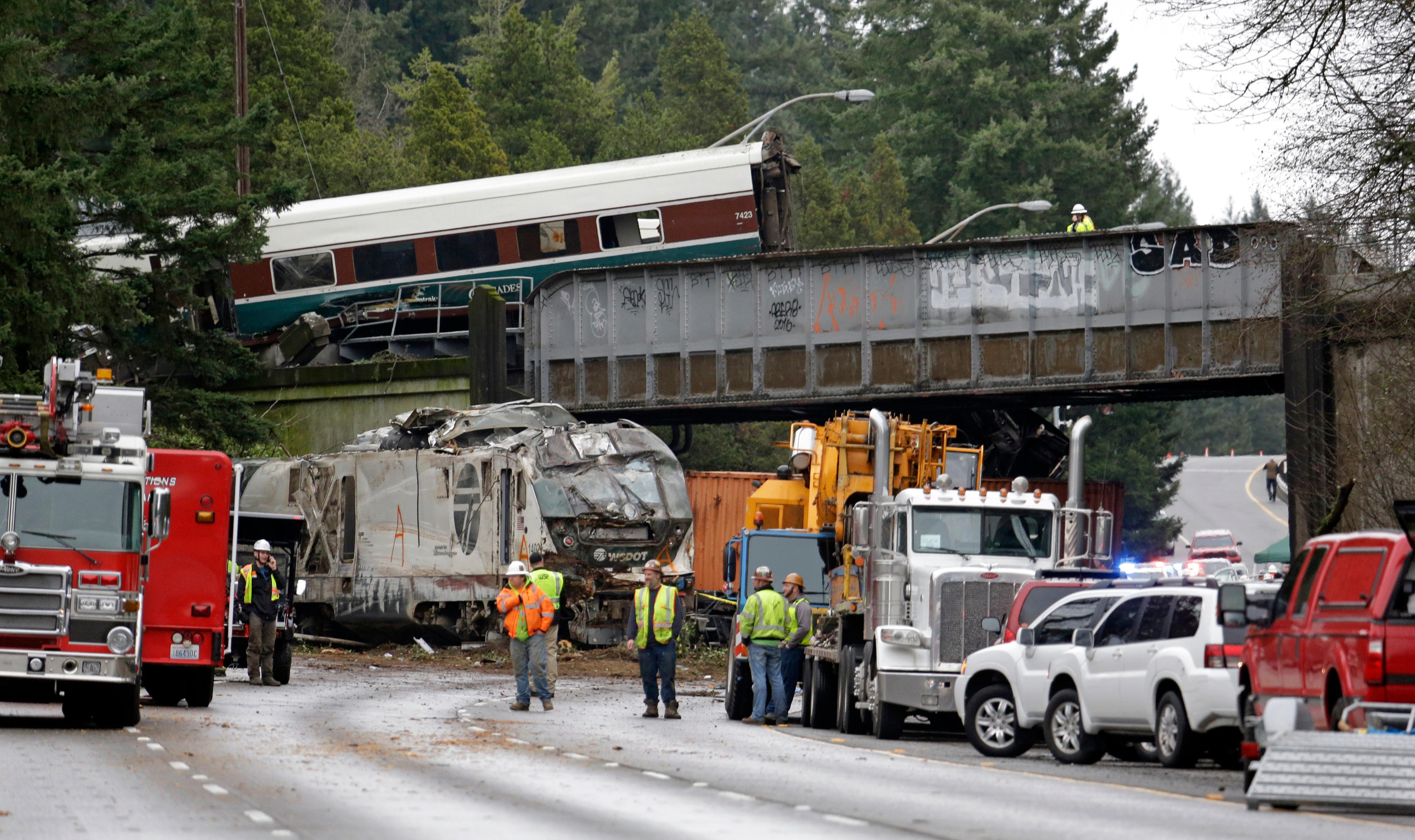 Cars from an Amtrak train lay spilled onto Interstate 5 below as some train cars remain on the tracks above Monday, Dec. 18, 2017, in DuPont, Wash. The Amtrak train making the first-ever run along a faster new route hurtled off the overpass Monday near Tacoma and spilled some of its cars onto the highway below, killing some people, authorities said. (AP Photo/Elaine Thompson)
