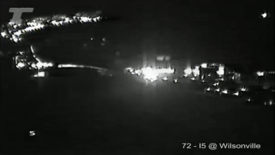 A screen capture from an ODOT camera shows flashing police lights and the backup on Interstate 5 in Wilsonville on Tuesday night. (ODOT)