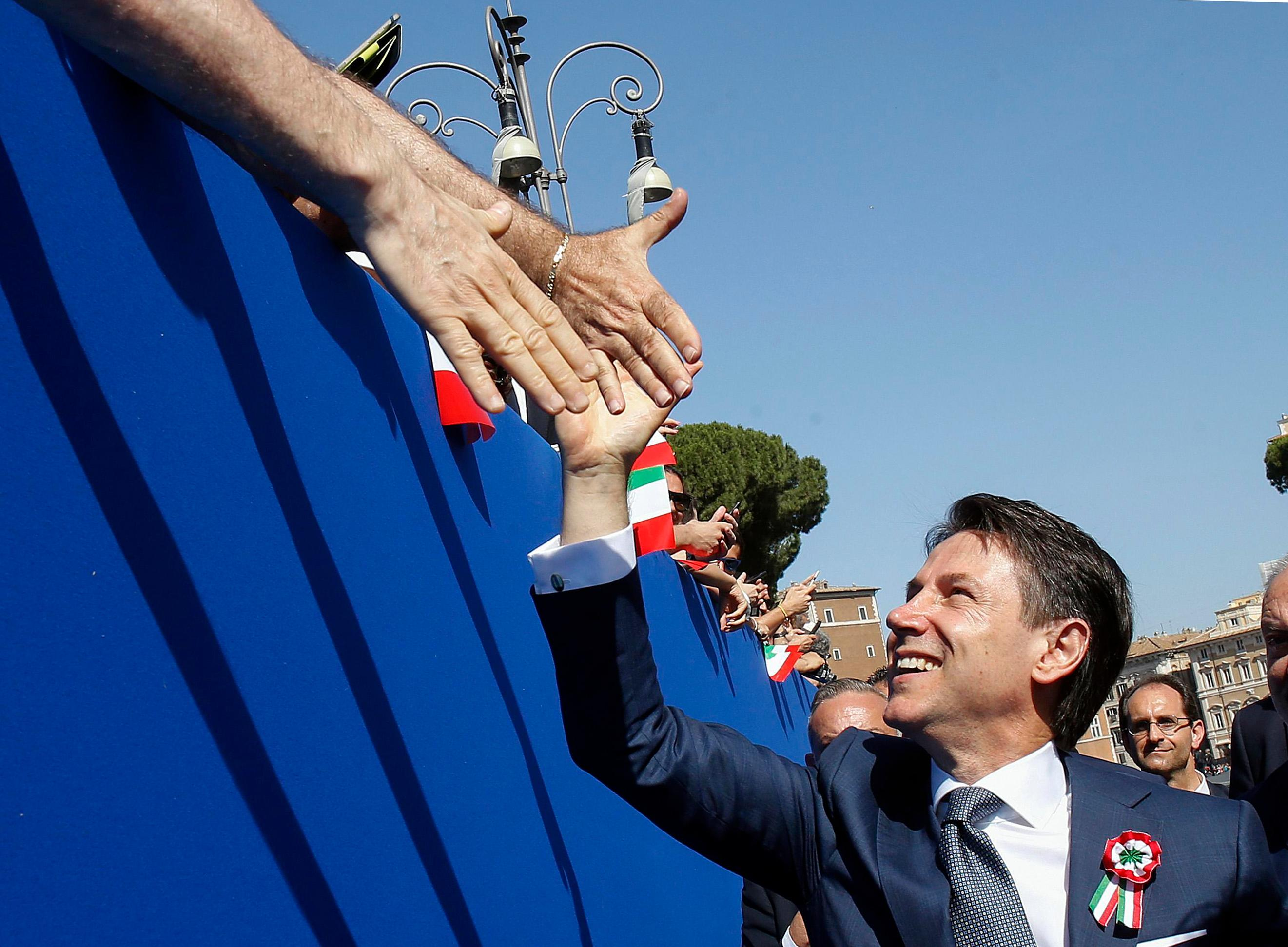 Italian Premier Giuseppe Conte is cheered by citizens on the occasion of the celebrations for Italy's Republic Day, in Rome Saturday, June 2, 2018.{ } (Fabio Frustaci/ANSA via AP)