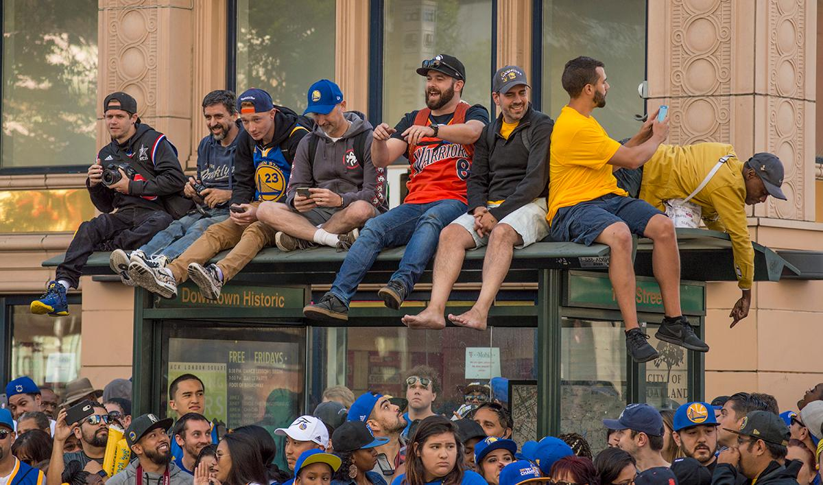 Fans on 13th Street in Oakland, California climb on top of a bus stop to get a better view of the Golden State Warriors victory parade. Photo by Emily Gonzalez, Oregon News Lab.