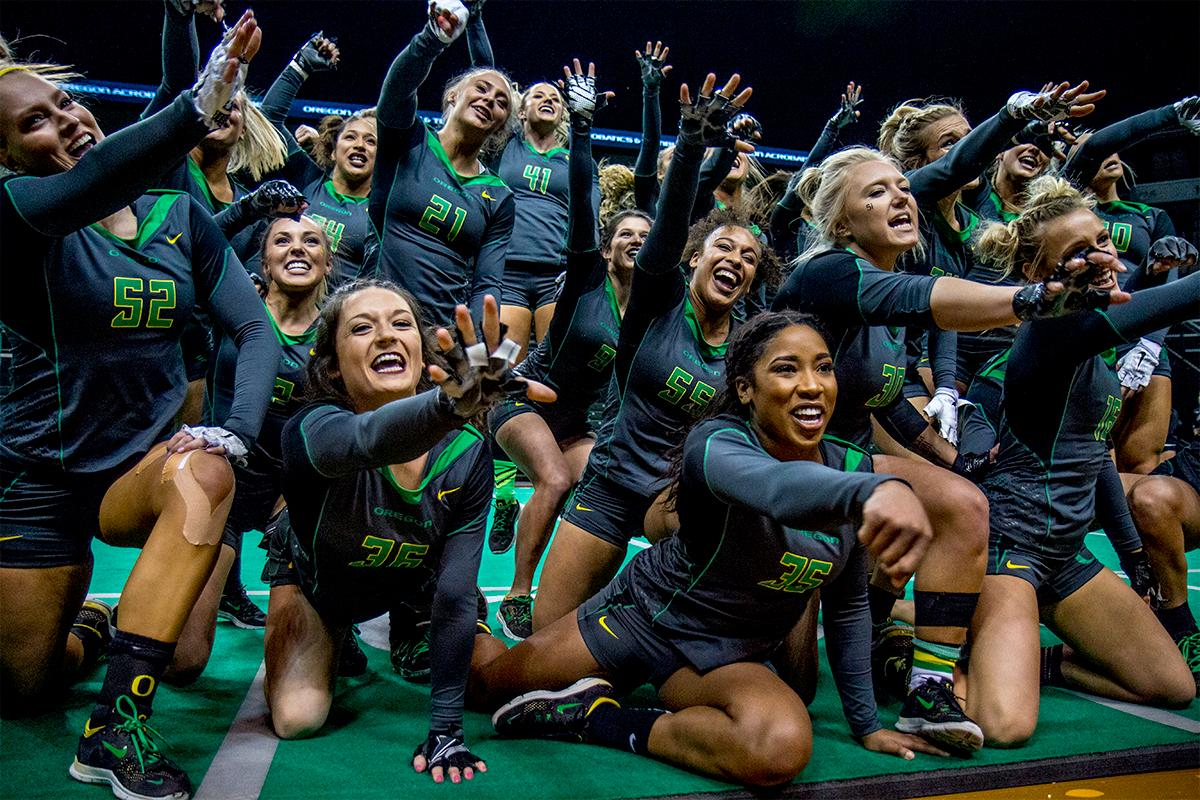 The Ducks Acrobatics and Tumbling Team punches the air in the final of the team routine. At their last home meet of the year and on Senior Night, the Ducks Acro and Tumbling Team defeated the Azusa Pacific Cougars, winning in all six categories: 38.70 to 37.20 in Compulsory; 29.35 to 28.60 in Acro; 29.40 to 29.35 in Pyramid; 29.35 to 28.95 in Toss; 57.525 to 66.15 in Tumbling; 103.75 to 98.03 in Team Routine; for an overall total of 288.08 to 277.28. The Ducks finished the season 6-1 and will next compete in the NCATA National Championship at Azusa, California April 27-29. Photo by August Frank, Oregon News Lab
