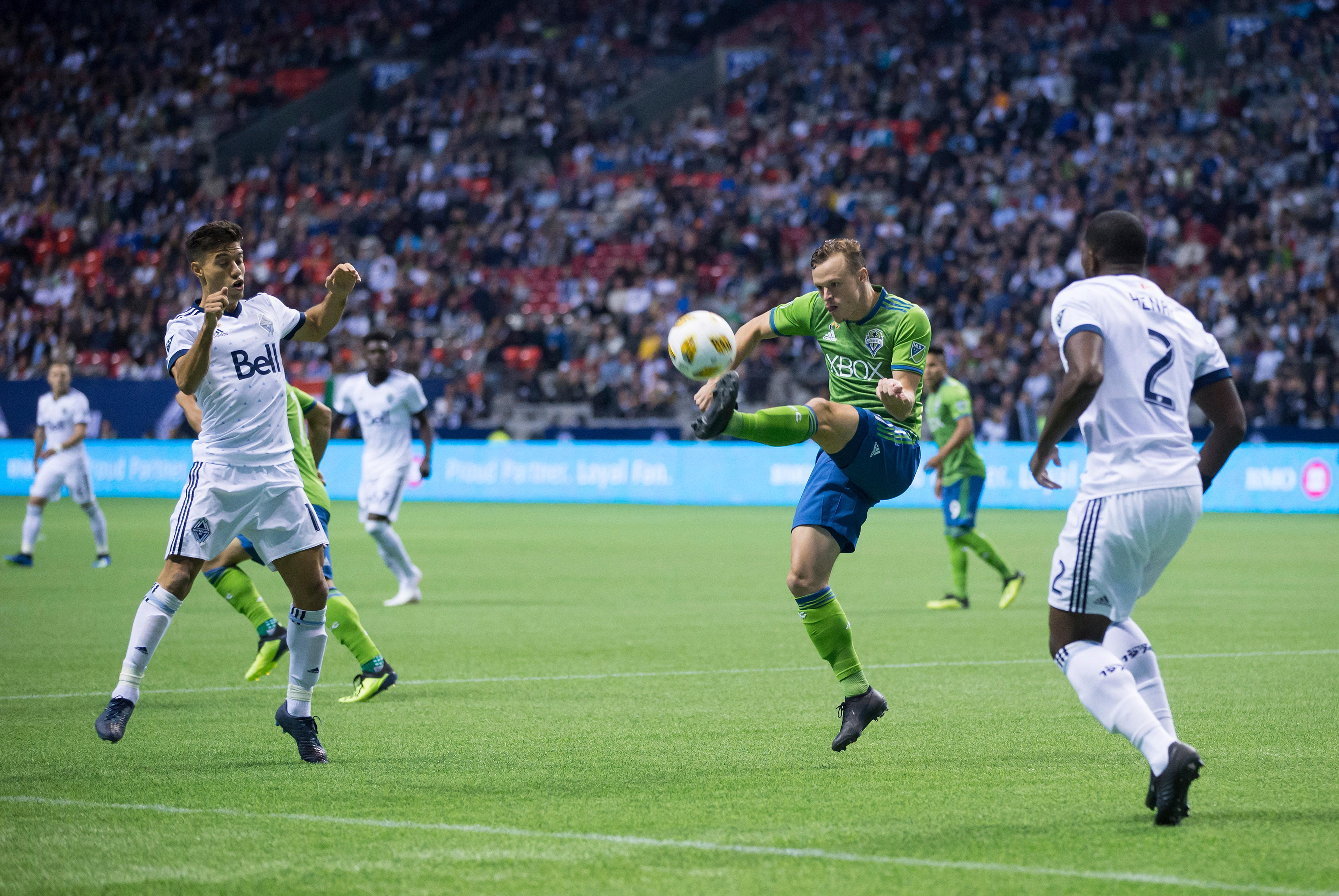 Seattle Sounders' Brad Smith, second from right, kicks the ball away from Vancouver Whitecaps' Nicolas Mezquida, left, and Doneil Henry, right, during the first half of an MLS soccer match, Saturday, Sept. 15, 2018, in Vancouver, British Columbia. (Darryl Dyck/The Canadian Press via AP)