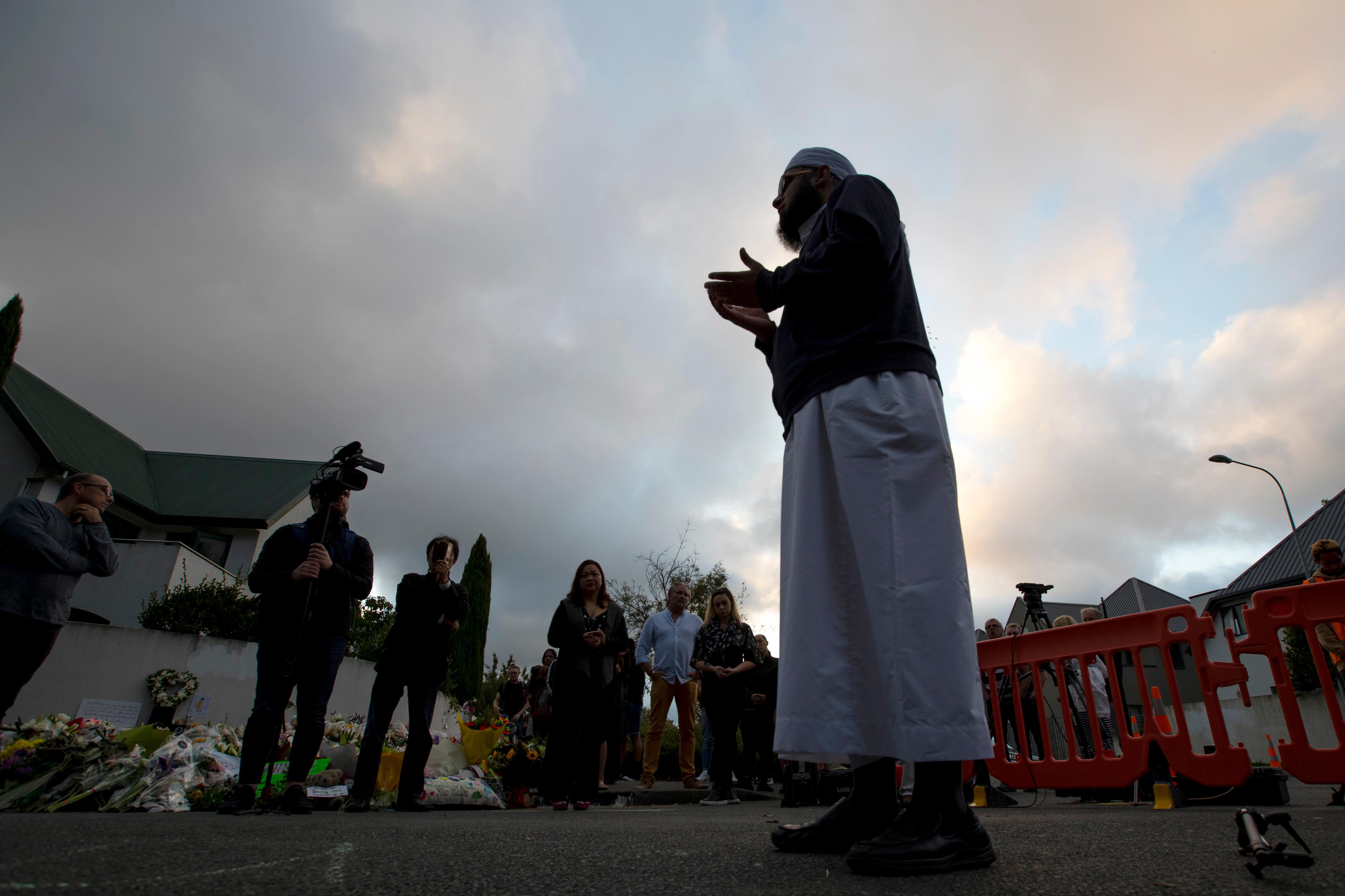 A Muslim offers prayer near the main road to the Al Noor mosque in Christchurch, New Zealand, Tuesday, March 19, 2019. Streets near the hospital that had been closed for four days reopened to traffic as relatives and friends of the victims of last week's mass shootings continued to stream in from around the world. (AP Photo/Vincent Thian)