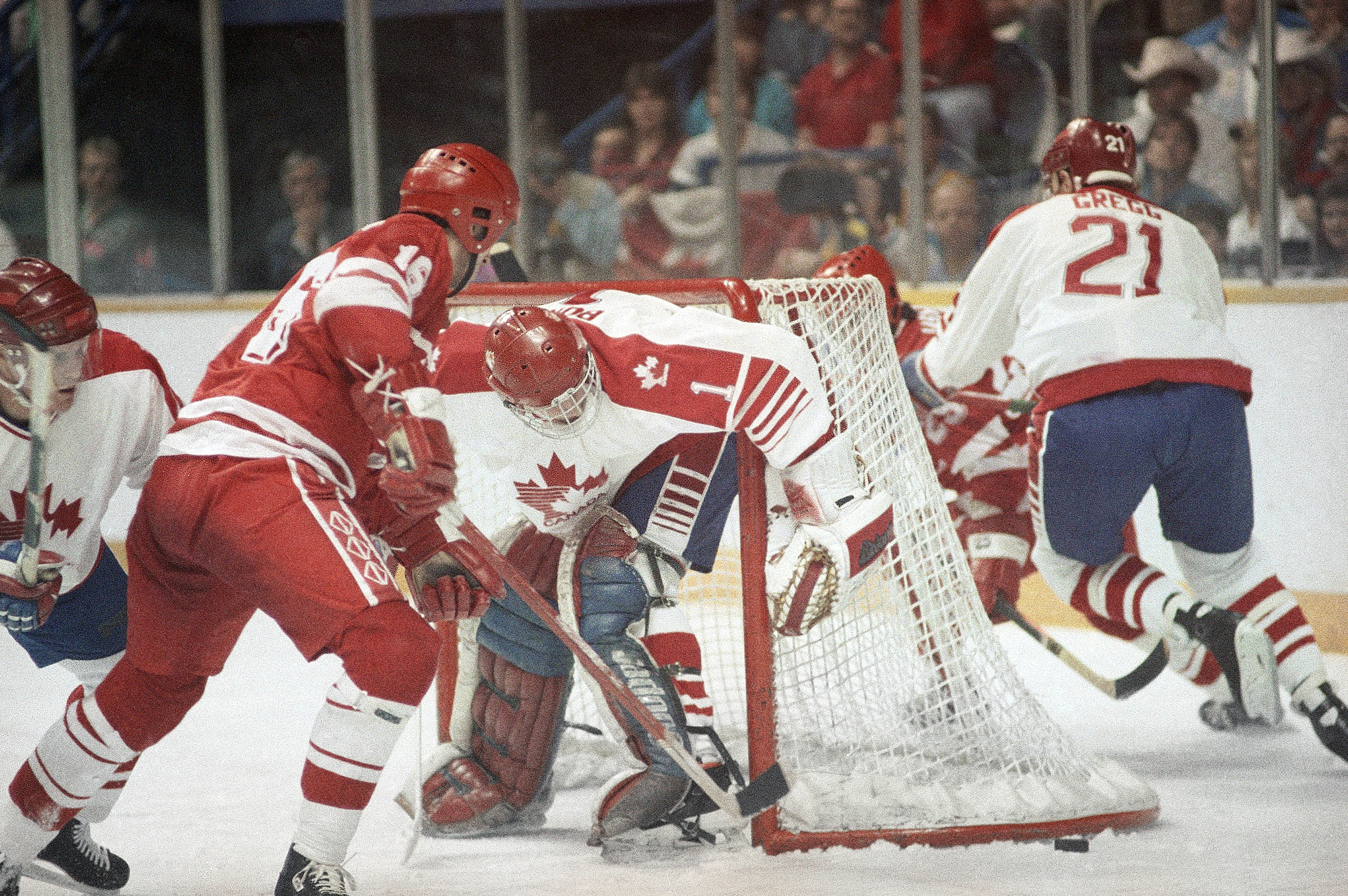 FILE - In this Feb. 24, 1988, file photo, a loose puck lies outside of the Canadian goal as Canadian goaltender Sean Burke and Soviet Union's Sergei Svetlov, left, go for it during an Olympic ice hockey medal round match at the Saddledome in Calgary. The 2018 Winter Games in Pyeongchang, South Korea will present a much different situation from any previous Olympic men's hockey tournament in history. Before NHL players began participating in 1998, national teams were centralized and spent months together, much like women's teams now, and the past five Olympics featured quick turnarounds on and off the 82-game NHL season. Because almost everyone in this tournament is playing professionally or in college, there isn't much of an opportunity for training camps _ though Canada, Russia and other countries are making the most of any time they have to get together. (AP Photo/File)