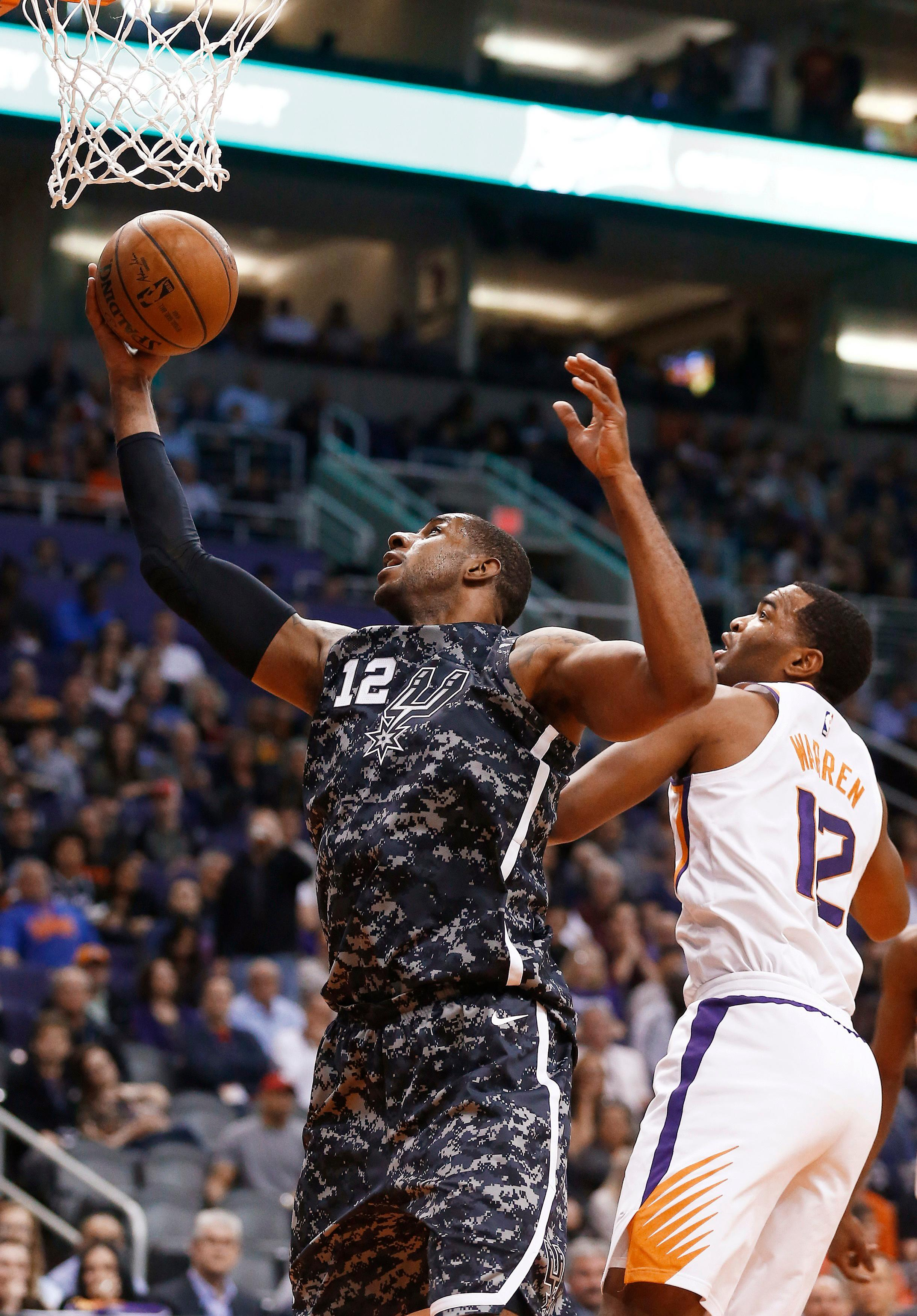 San Antonio Spurs forward LaMarcus Aldridge, left, drives past Phoenix Suns forward TJ Warren, right, to score during the first half of an NBA basketball game Wednesday, Feb. 7, 2018, in Phoenix. (AP Photo/Ross D. Franklin)