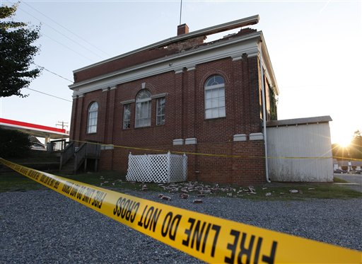 The sun sets behind a quake damaged building in Mineral, Va., a small town close to the epicenter, Tuesday. / AP photo