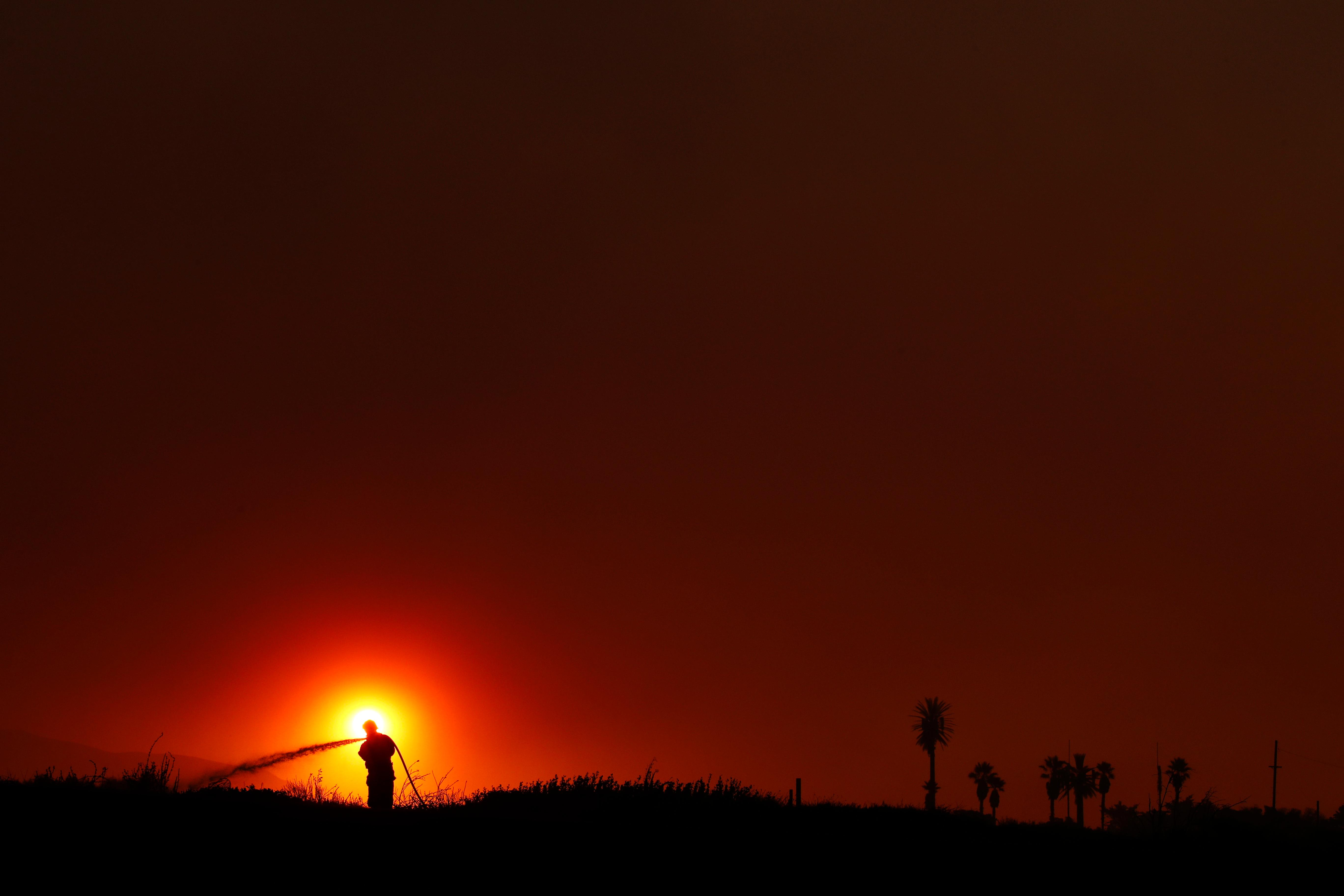 Firefighter Dan Whelan is silhouetted against the sun as he battles a wildfire burning near Faria State Beach in Ventura, Calif., Thursday, Dec. 7, 2017. The wind-swept blazes have forced tens of thousands of evacuations and destroyed dozens of homes. (AP Photo/Jae C. Hong)