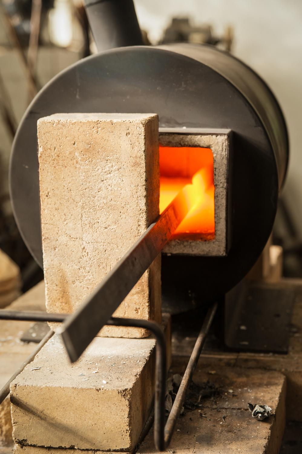 A bar of steel gathers heat inside the forge. / Image: Melissa Doss Sliney