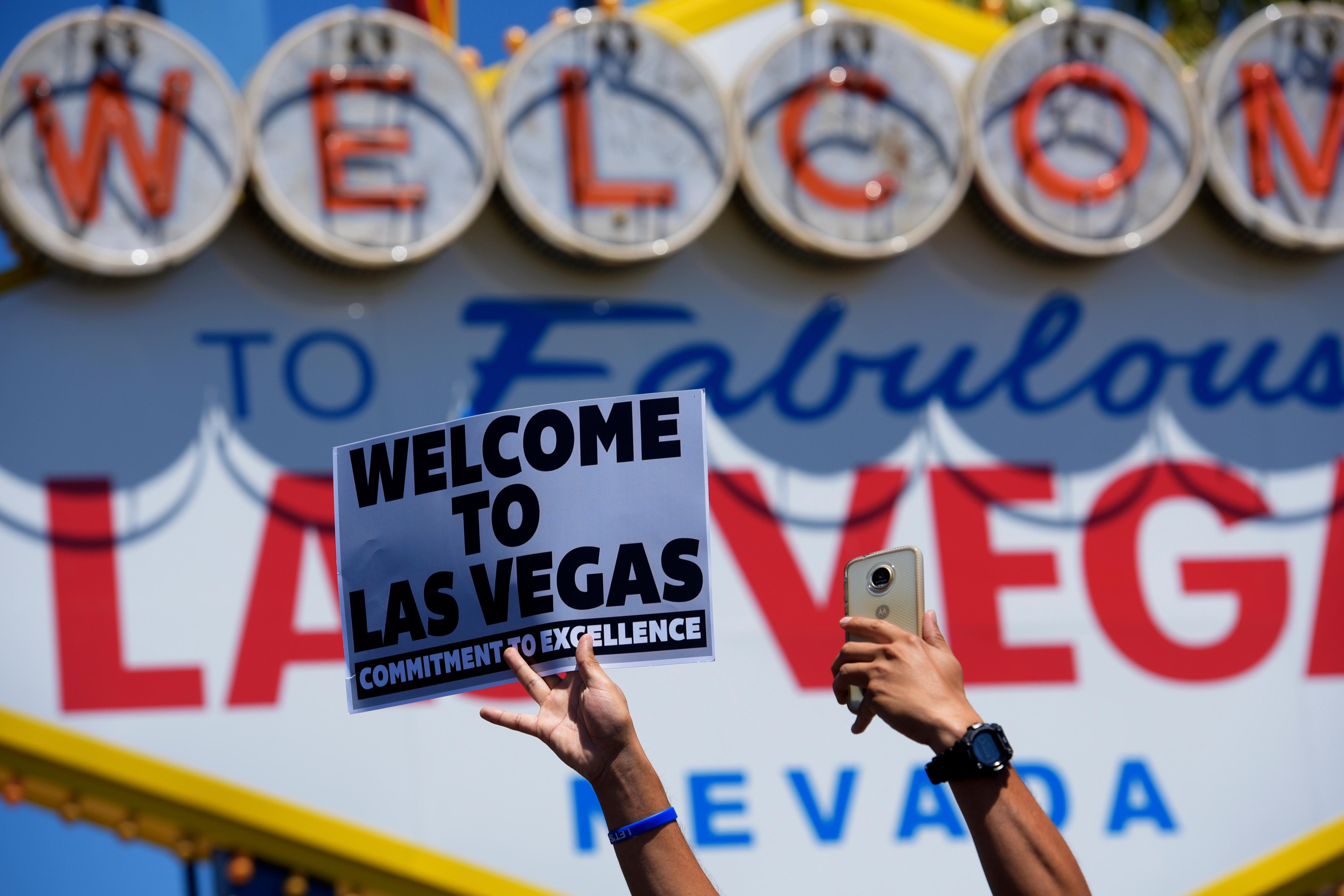 "A Raiders fan holds up a sign as the Raiders fifth round draft pick is announced in front of the ""Welcome to Fabulous Las Vegas"" sign Saturday, April 28, 2017. [Sam Morris/Las Vegas News Bureau]"