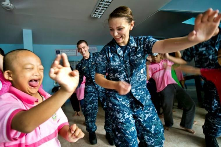 U.S. Navy Seaman Erin Ziegler dances with a child at Khun Boonchu Home for Autistic Children during a community service project in Pattaya, Thailand. Ziegler is a gas turbine system technician fireman assigned to the guided-missile destroyer USS Mustin.