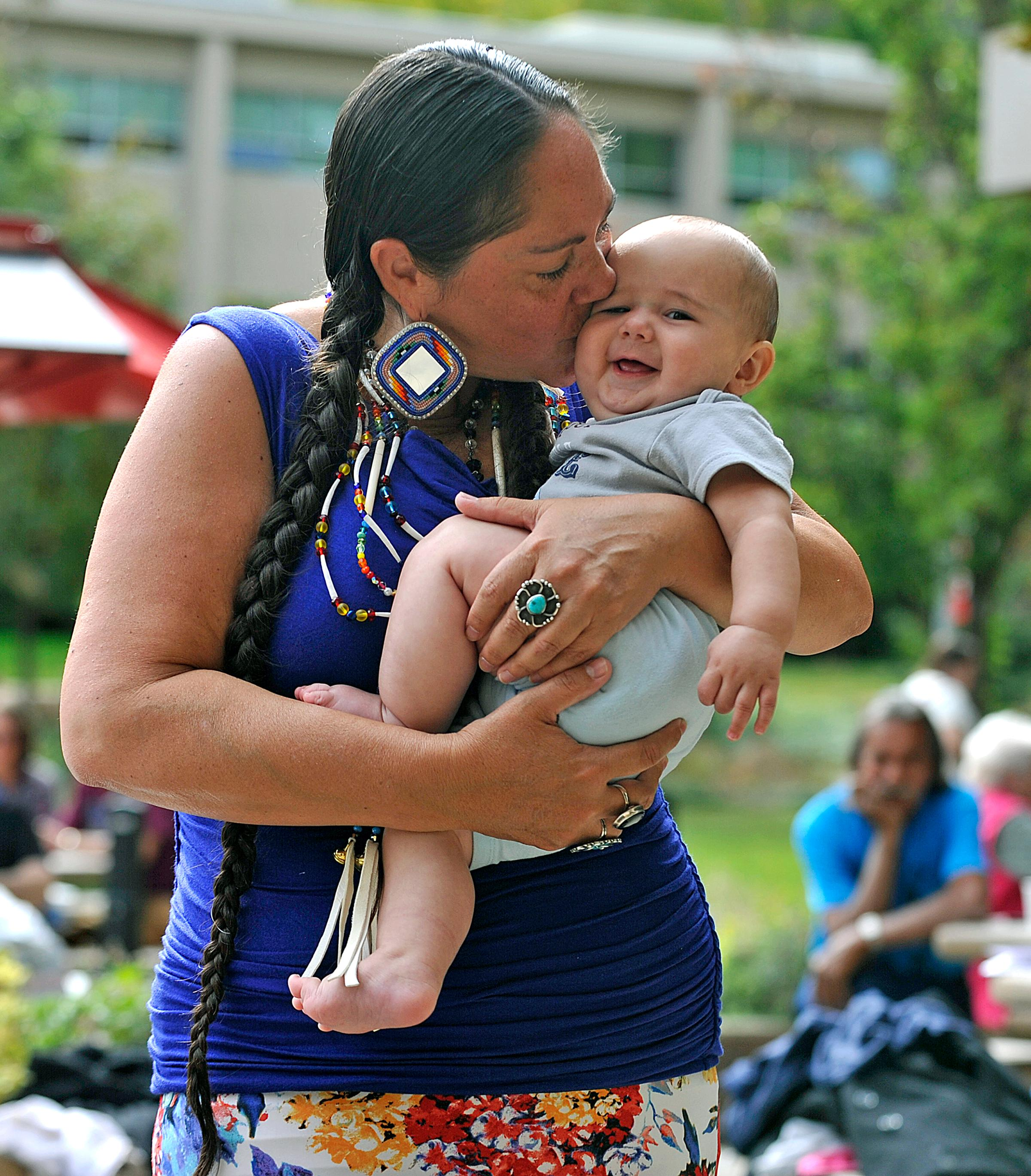 Lupe Sims snuggles with her son Cedar Sims-Smith during Indigenous Peoples Day at Southern Oregon University. Daily Tidings / Jamie Lusch