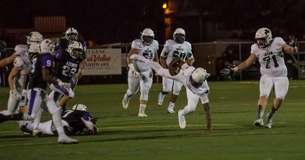 Sheldon Irish offensive linemen Austin Lasby (#51) and Donovan Scurlock (#60) watch as the ball carrier falls during a play.                  The Sheldon Irish defeated the South Eugene Axemen 63-6 at South on Friday night. Photo by Abigail Winn, Oregon News Lab