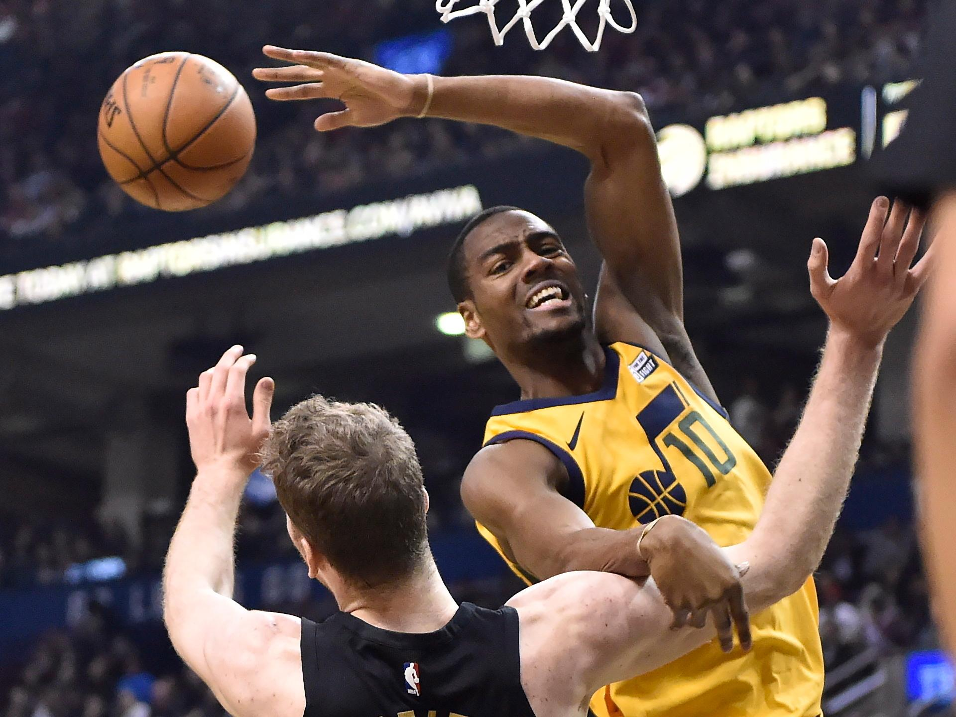 Utah Jazz guard Alec Burks (10) passes the ball as Toronto Raptors center Jakob Poeltl (42) defends during the first half of an NBA basketball game Friday, Jan. 26, 2018, in Toronto. (Frank Gunn/The Canadian Press via AP)