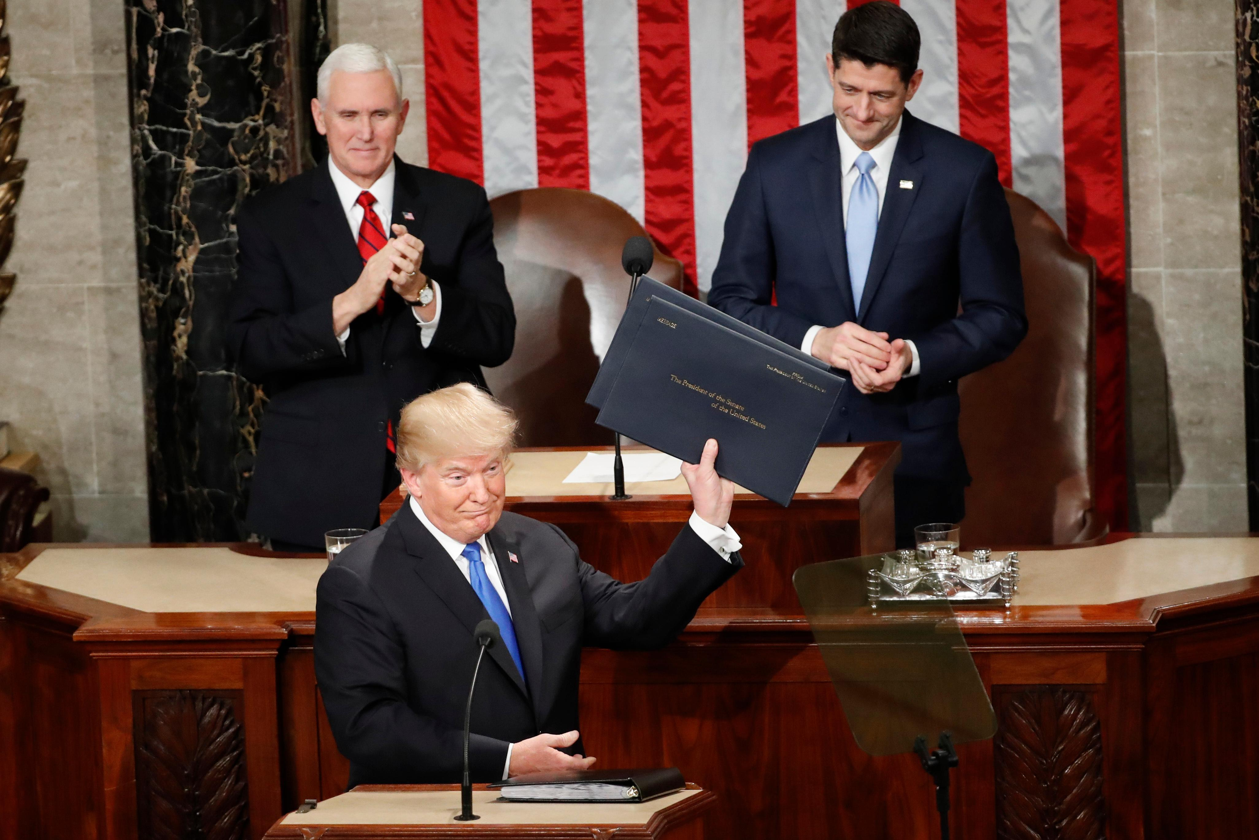 President Donald Trump holds up copies of his speech before the State of the Union address to a joint session of Congress on Capitol Hill in Washington, Tuesday, Jan. 30, 2018. (AP Photo/Pablo Martinez Monsivais)