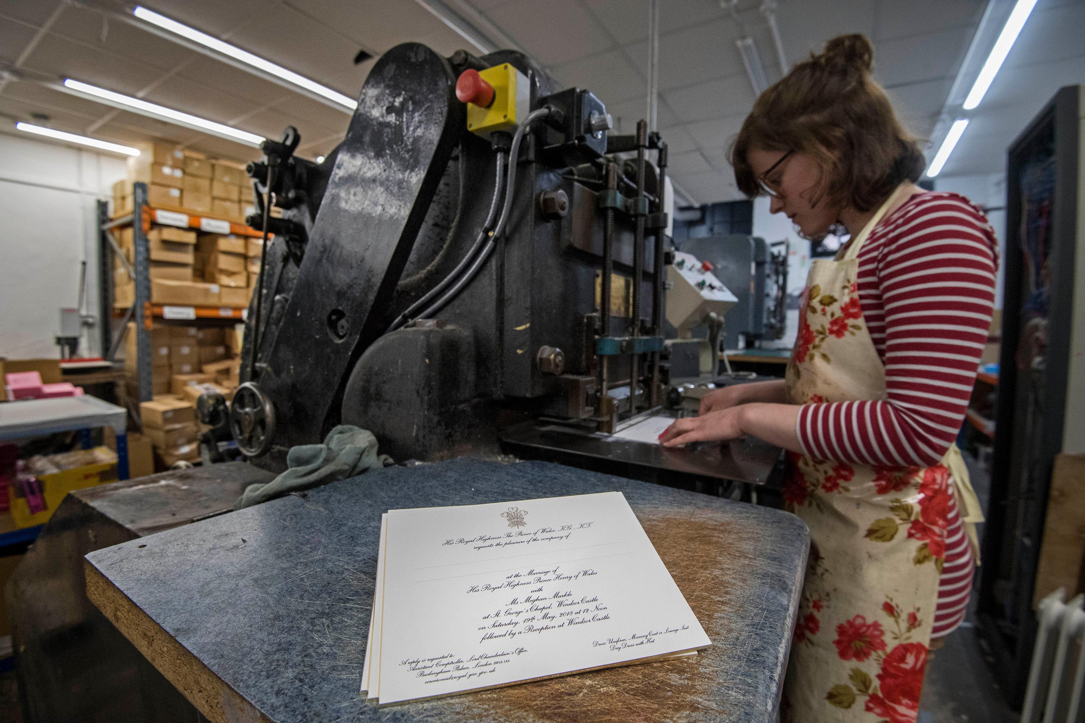 Lottie Small use the die stamping press at the workshop of Barnard and Westwood in London, who are printing the invitations for Prince Harry and Meghan Markle's wedding in May, Thursday March 22, 2018. Prince Harry and Meghan will get married at St George's Chapel  in Windsor Castle on Saturday  May 19. (Victoria Jones/Pool via AP)