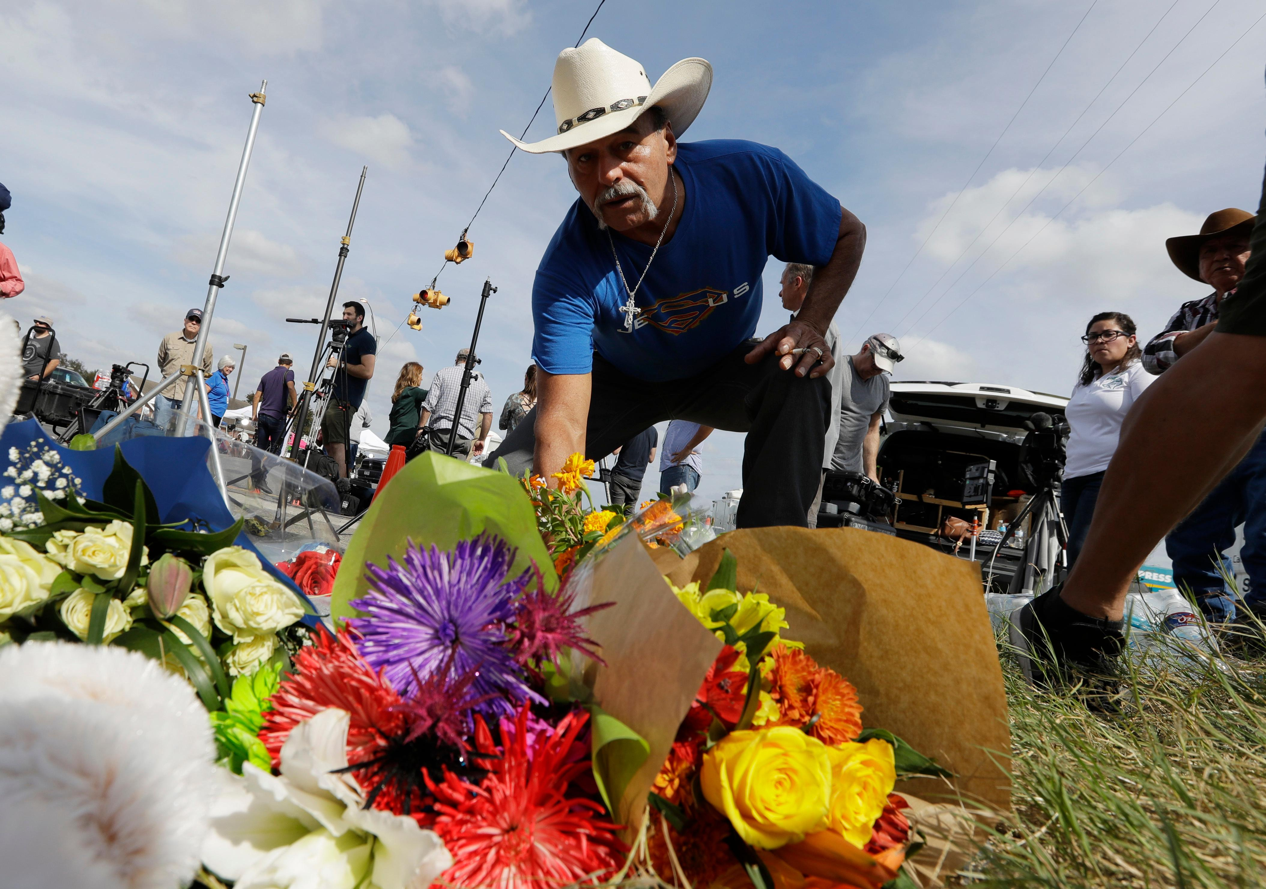 Rene Moreno drops off flowers at a makeshift memorial at the scene of a shooting at the First Baptist Church of Sutherland Springs, Tuesday, Nov. 7, 2017, in Sutherland Springs, Texas. A man opened fire inside the church in the small South Texas community on Sunday, killing more than two dozen and injuring others. (AP Photo/Eric Gay)