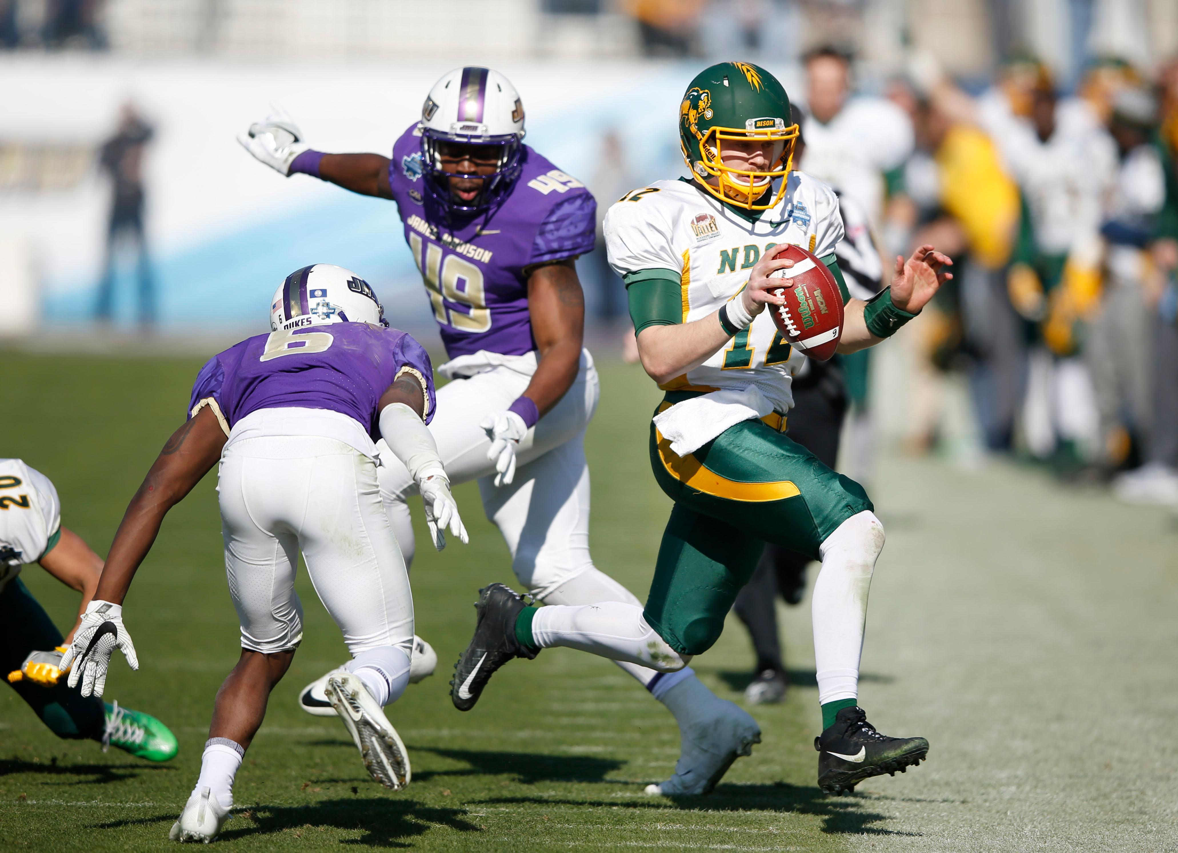 North Dakota State quarterback Easton Stick (12) runs out of bounds after making the first down as James Madison cornerback Jimmy Moreland (6) closes in on the play during the first half  in the FCS championship NCAA college football game at Toyota Stadium in Frisco, Texas, Saturday, Jan. 6, 2017. (Vernon Bryant/The Dallas Morning News via AP)