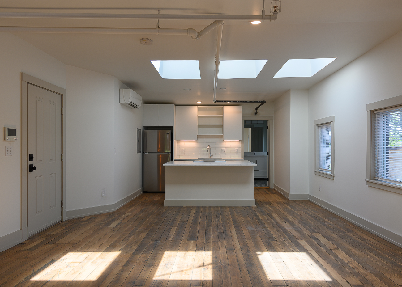 On the top floor, this 648-square-foot studio apartment rents for $850/month. Three skylights draw in natural light to illuminate the floor's original hardwood floors. The kitchen is outfitted with Samsung appliances, and a large bathroom with a shower stall and an all-in-one LG washer/dryer unit is concealed behind a closet door. A sloping ceiling adds character to the living/bedroom with industrial wall sconces to help light the corner between windows. Contact Greg Cole at gcole@theacanthusgroup.com to inquire about renting at 1925 Vine Street. / Image: Phil Armstrong, Cincinnati Refined // Published: 5.9.19