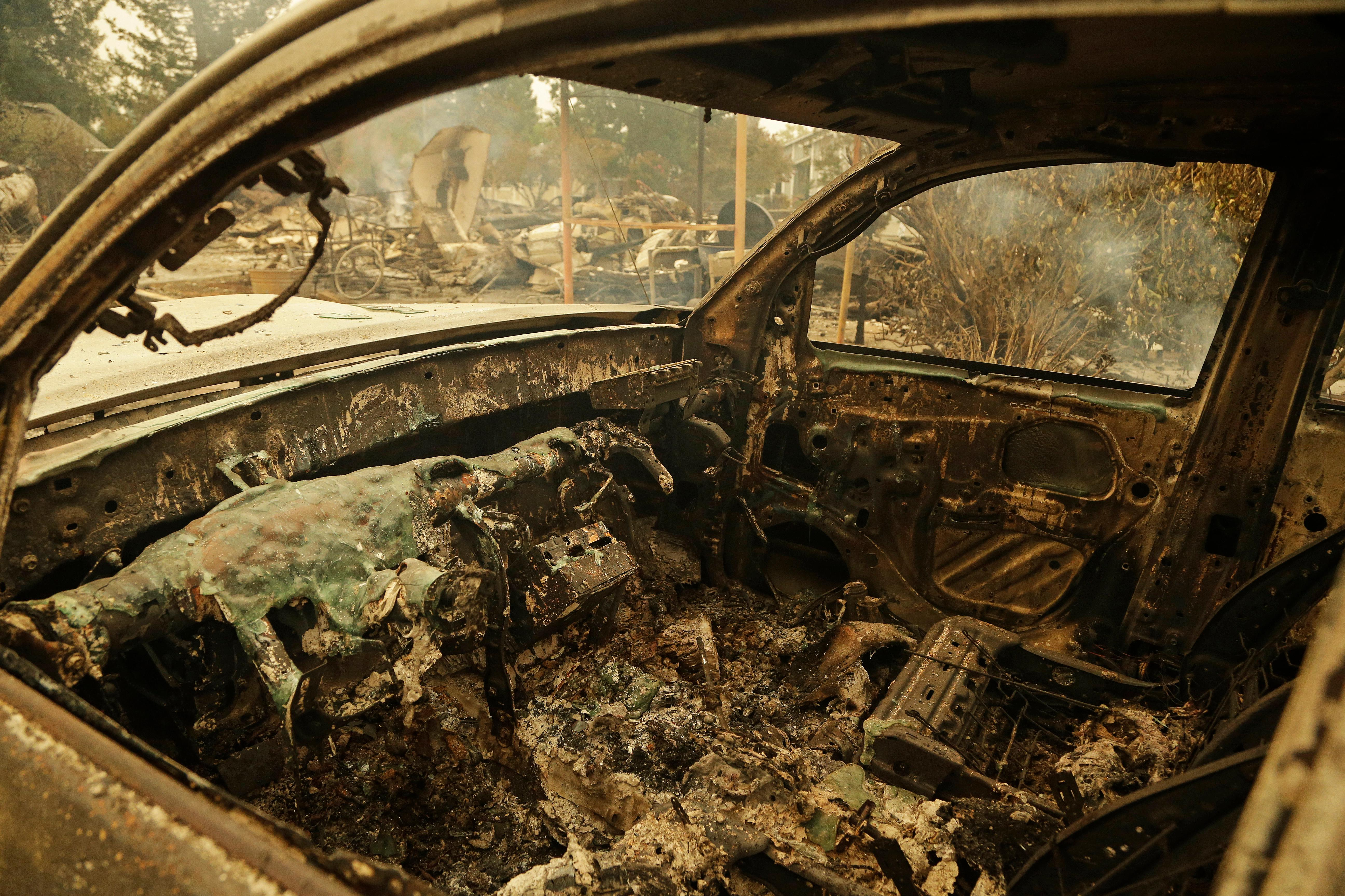 The remains of an automobile sit in the Coffey Park area of Santa Rosa, Calif. An onslaught of wildfires across a wide swath of Northern California broke out almost simultaneously then grew exponentially, swallowing up properties from wineries to trailer parks and tearing through both tiny rural towns and urban subdivisions. (AP Photo/Ben Margot)