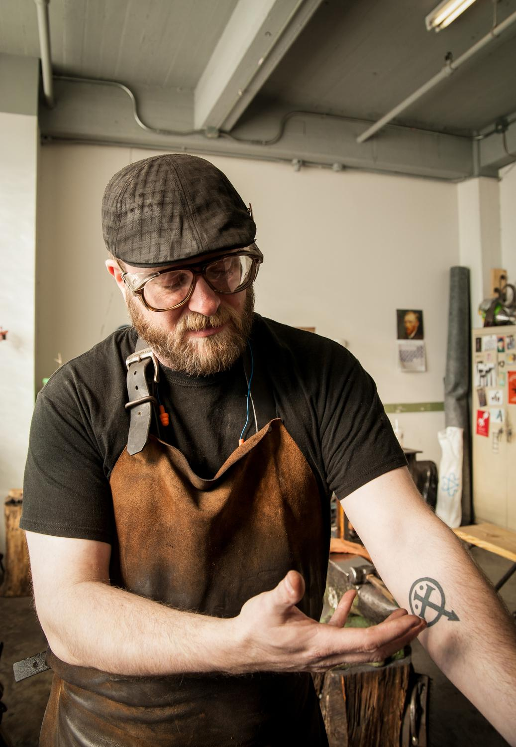 "Artist-blacksmith Mark Gilsdorf explains his tattoo: ""My tattoo combines the alchemist's symbol for iron with the sign for the Roman god Mars, from which the name Mark is derived. So they all kind of blend together to represent me."" / Image: Melissa Doss Sliney"