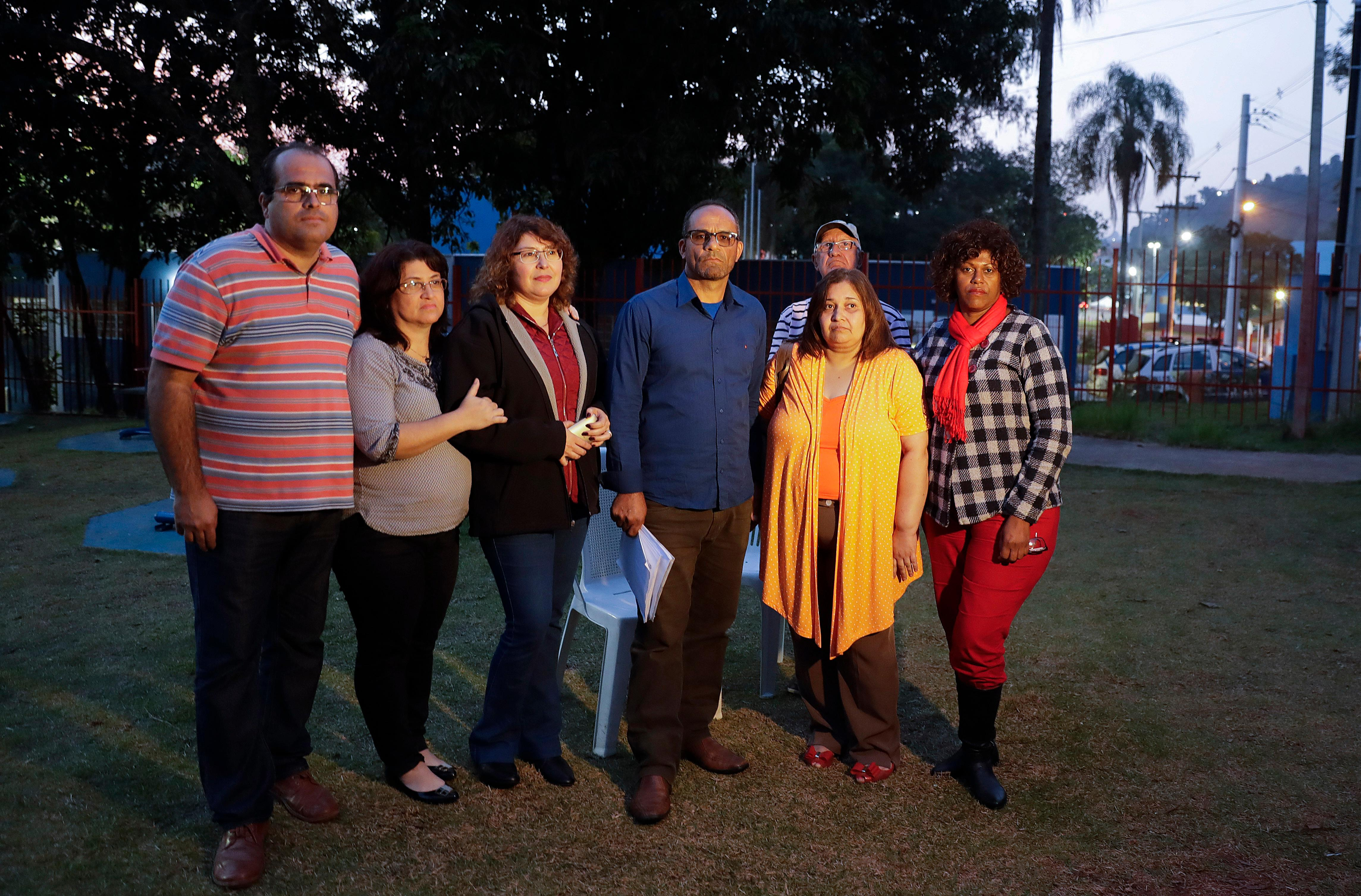 FILE - In this Sunday, May 28, 2017 photo, former members of the Rhema Community Evangelical Ministry, from left, Marcelo Galvao Machado, Tania Machado, Naara Abe, Flavio Correa de Souza, Carlos, Rosangela Ferreira Souza, and Maria Reis, stand in a park in Franco da Rocha, Brazil, in the greater Sao Paulo area. Over the course of two decades, the U.S.-based Word of Faith Fellowship mother church took command of theirs and another congregation in Brazil, applying a strict interpretation of the Bible and enforcing it through rigorous controls and physical punishment, The Associated Press has found. (AP Photo/Andre Penner)