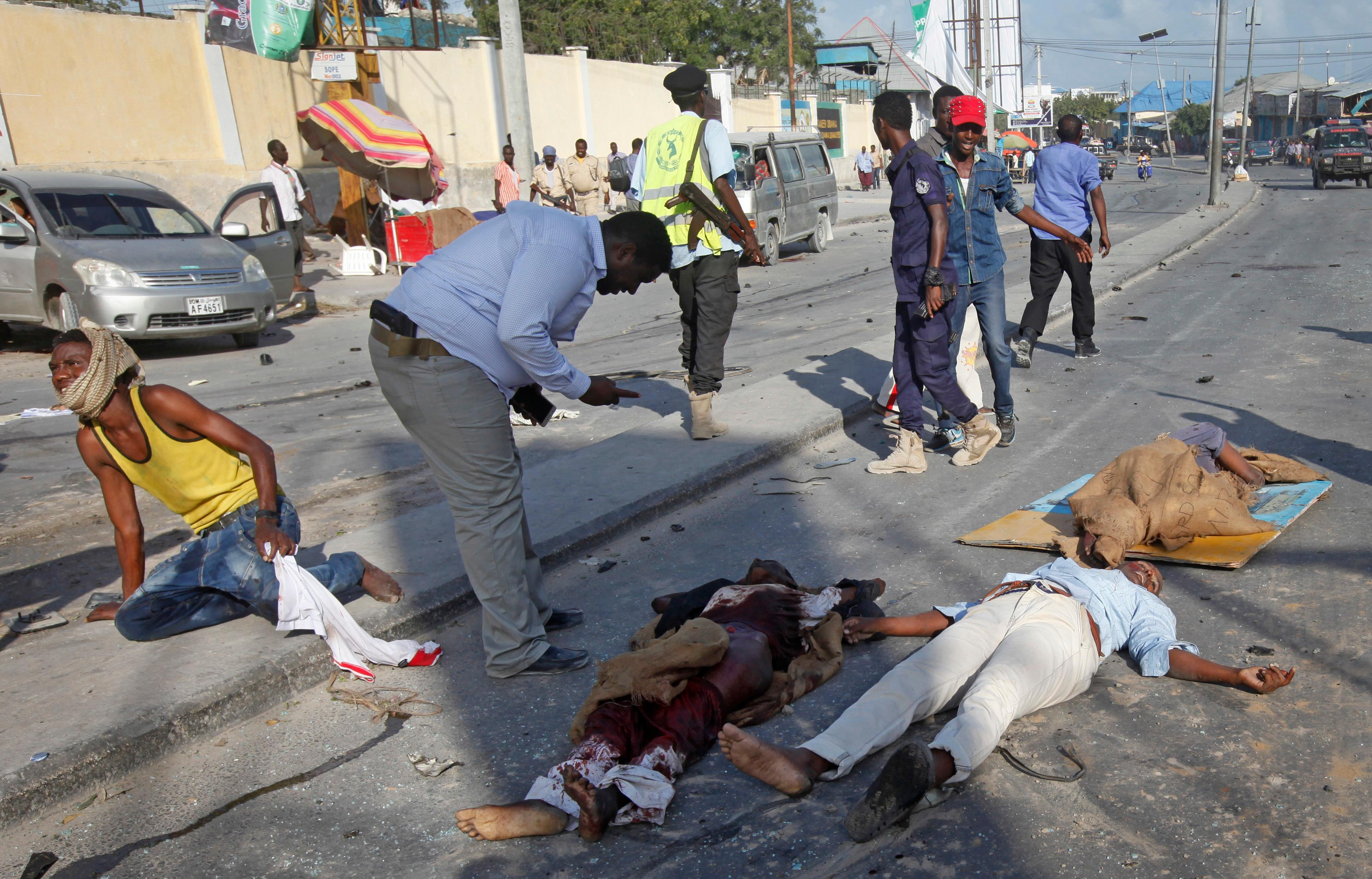 EDS NOTE GRAPHIC CONTENT Wounded and dead lie in the street at the scene of a blast in the capital Mogadishu, Somalia Saturday, Oct. 14, 2017. A huge explosion from a truck bomb has killed at least 20 people in Somalia's capital, police said Saturday, as shaken residents called it the most powerful blast they'd heard in years. (AP Photo/Farah Abdi Warsameh)