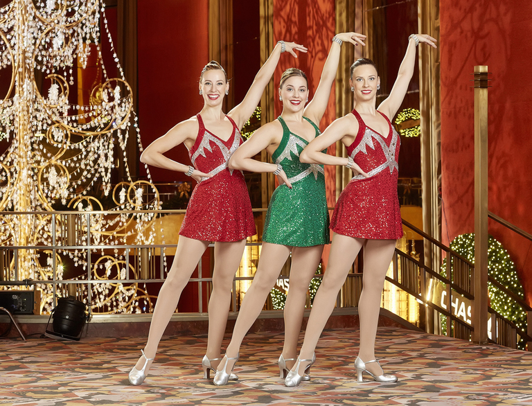 This Nov. 18, 2015 photo provided by Madison Square Garden Photo Services shows Radio City Rockettes, Kristin, from left, Alison and Lisa Jantzie, posing on the mezzanine at Radio City Music Hall during Radio City Christmas Spectacular in New York. The three long-legged, stunning sisters - including two identical twins - are in the lineup for the Radio City Christmas Spectacular.  (Carl Scheffel/MSG Photos via AP)