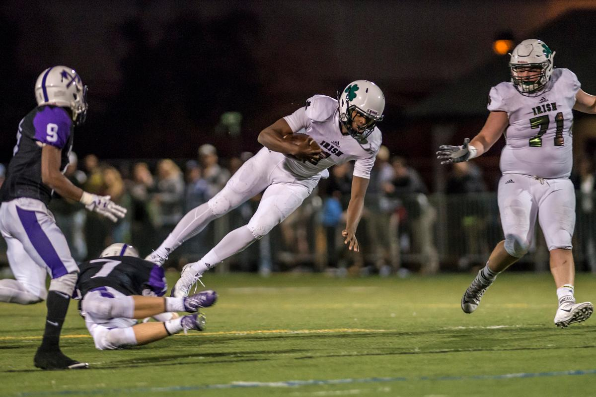 Sheldon Irish quarterback Michael Johnson leaps to avoid South Eugene Axemen's Bruyce Boettcher in their matchup at South Eugene high school, October 6, 2017. (Colin Houck/ For KVAL)