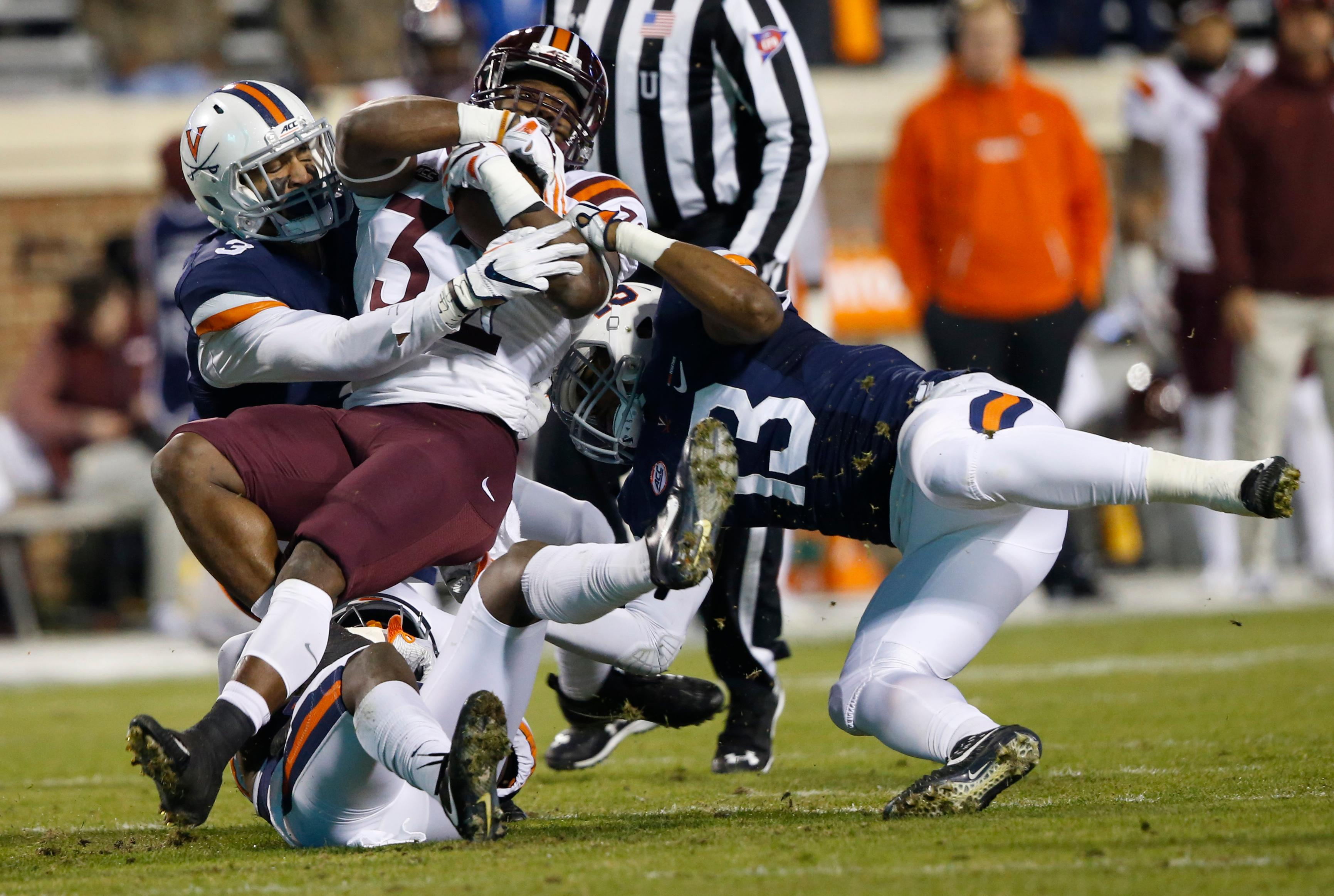 Virginia Tech running back Steven Peoples (32) gets wrapped up by Virginia linebacker Chris Peace (13) and safety Quin Blanding (3) during the first half of an NCAA college football game in Charlottesville, Va., Friday, Nov. 24, 2017. (AP Photo/Steve Helber)