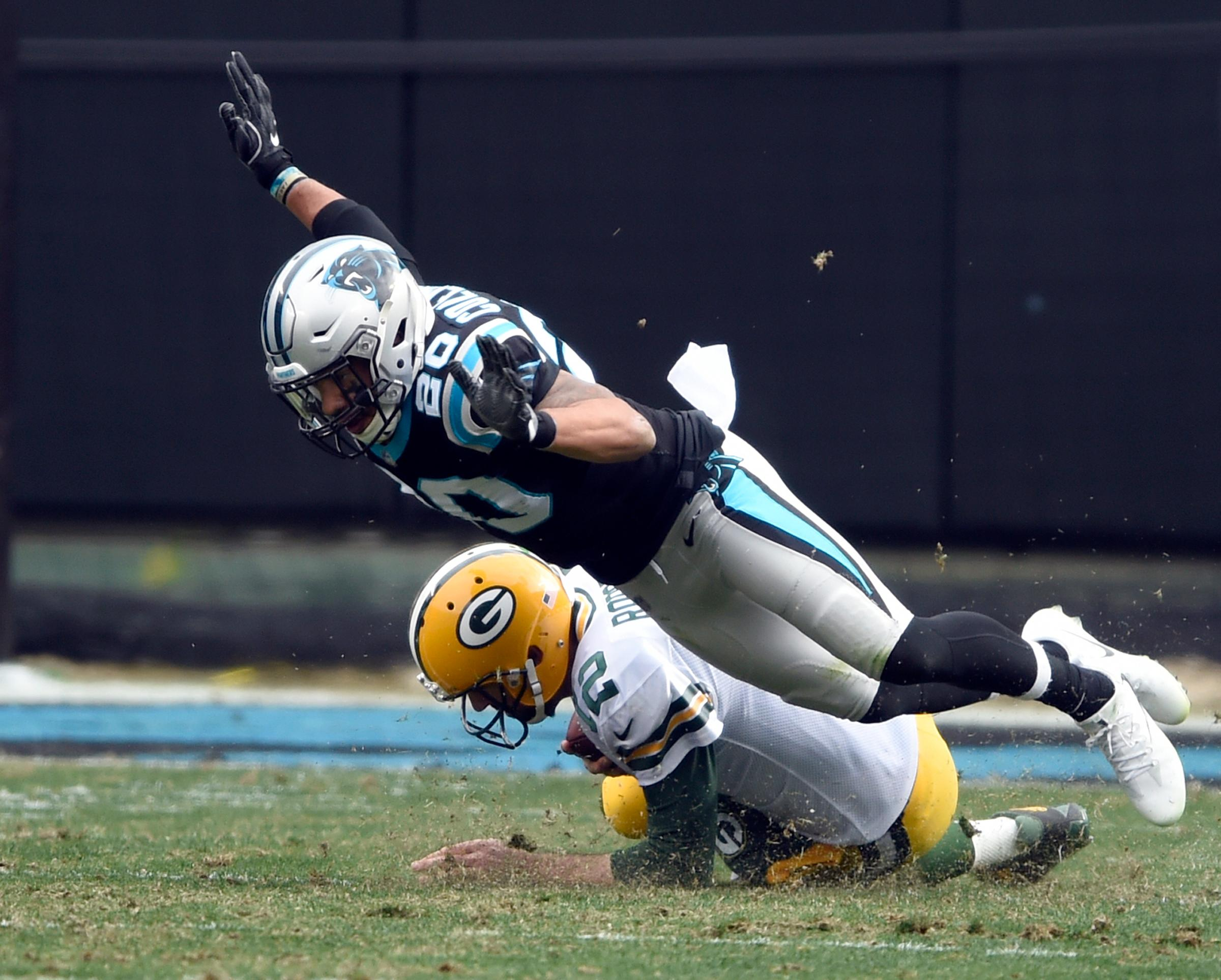 Carolina Panthers' Kurt Coleman (20) flies over a sliding Green Bay Packers' Aaron Rodgers (12) during the first half of an NFL football game in Charlotte, N.C., Sunday, Dec. 17, 2017. (AP Photo/Mike McCarn)