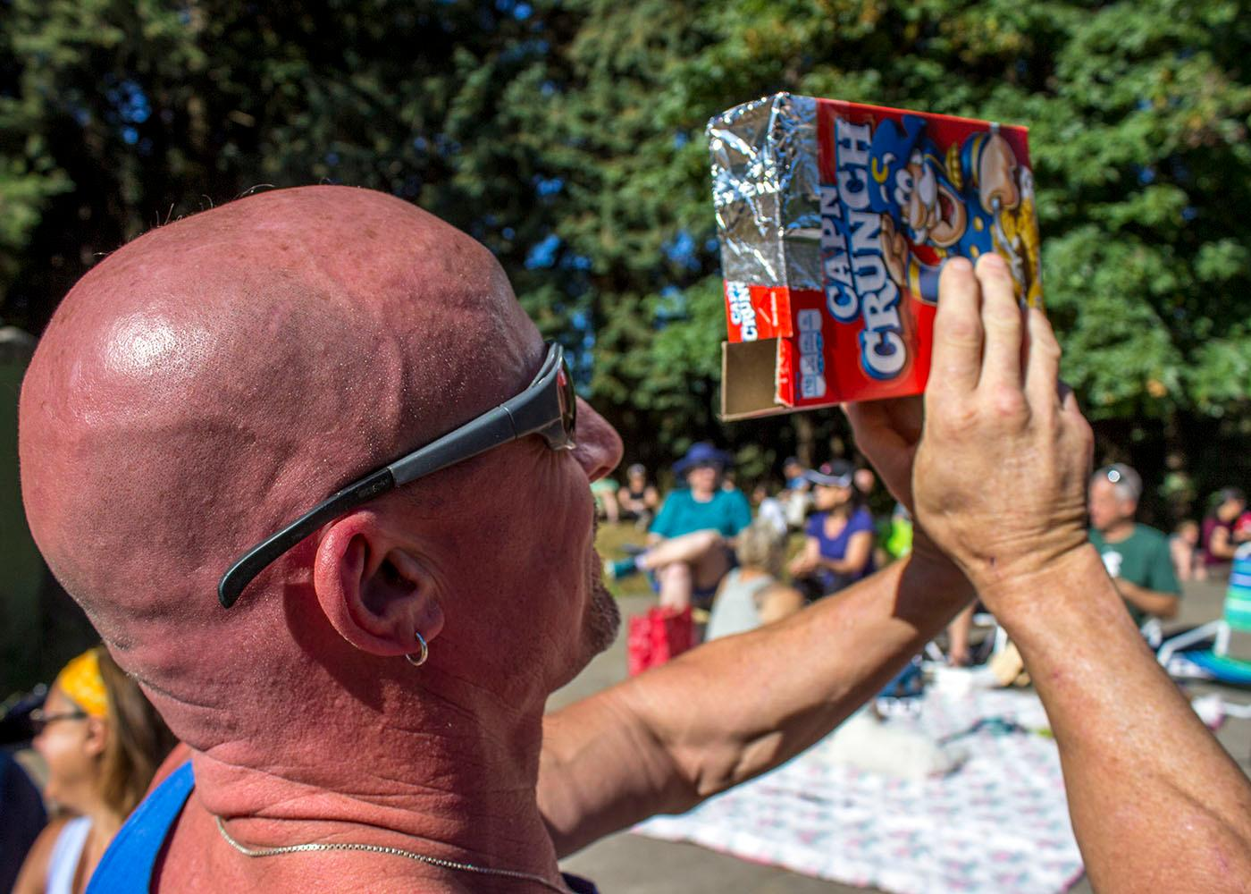 Although it wasn't in the path of totality, dozens of people gathered at Mt. Tabor in Portland, Ore. to watch the solar eclipse on August 21, 2017. In Portland, the moon covered 99.2 percent of the sun at 10:19 a.m. Spectators used glasses, filters and pinhole projectors to view the eclipse. Photo by Amanda Butt