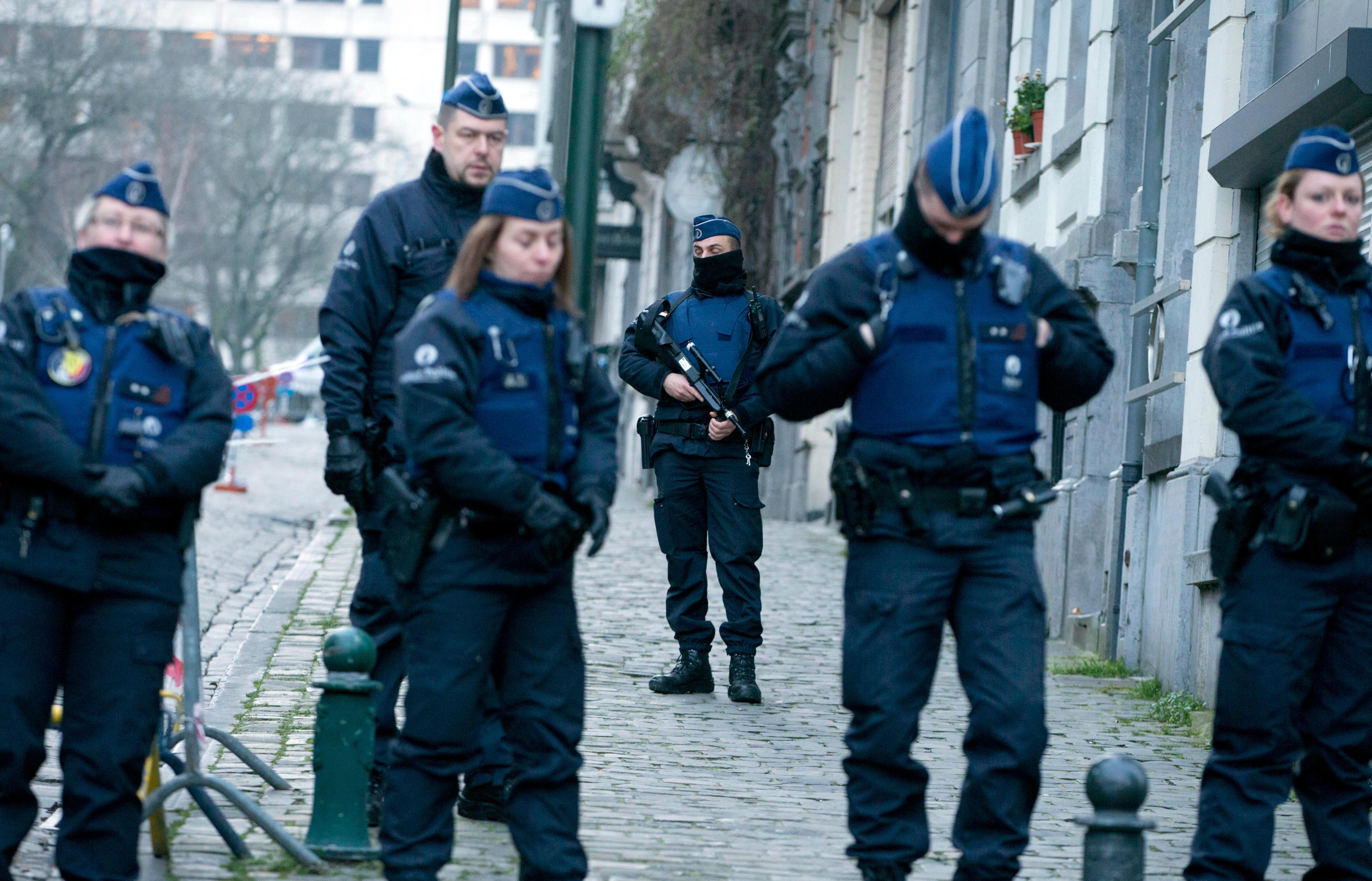 Police guard as they await a convoy carrying Salah Abdeslam and other members of the trial arrives under police guard at the Brussels Justice Palace in Brussels on Monday, Feb. 5, 2018. Salah Abdeslam and Soufiane Ayari face trial for taking part in a shooting incident in Vorst, Belgium on March 15, 2016. The incident took place when six members of a Franco-Belgian research team investigating the attacks in Paris were conducting a search in an allegedly empty safe house of the terrorists and were attacked. (AP Photo/Virginia Mayo)