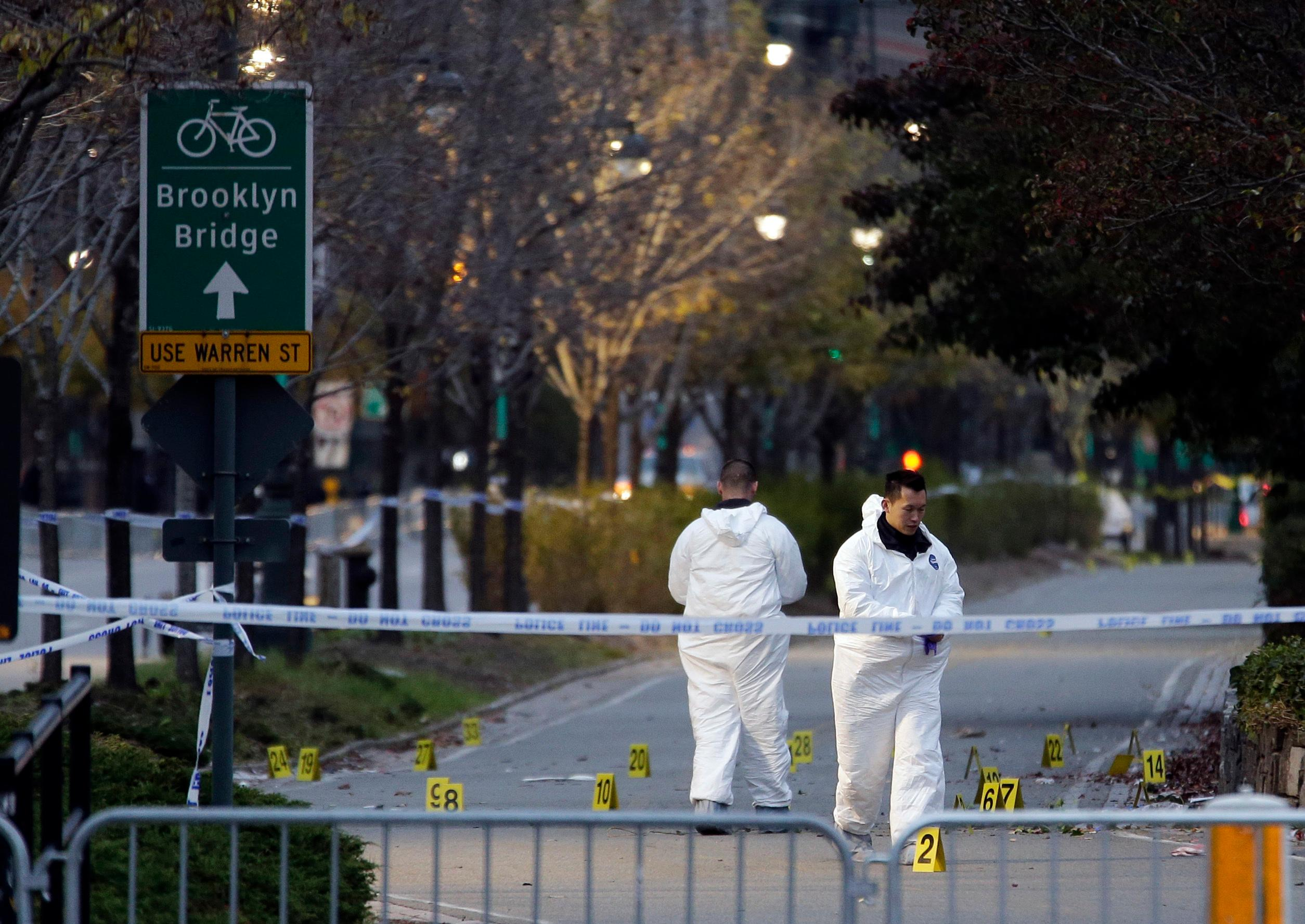 Emergency officials walk near evidence markers on the west side bike path in lower Manhattan, New York, Wednesday, Nov. 1, 2017. Investigators worked through the night to determine what led a truck driver to plow down people Tuesday on the riverfront bike path near the World Trade Center, authorities said. (AP Photo/Seth Wenig)